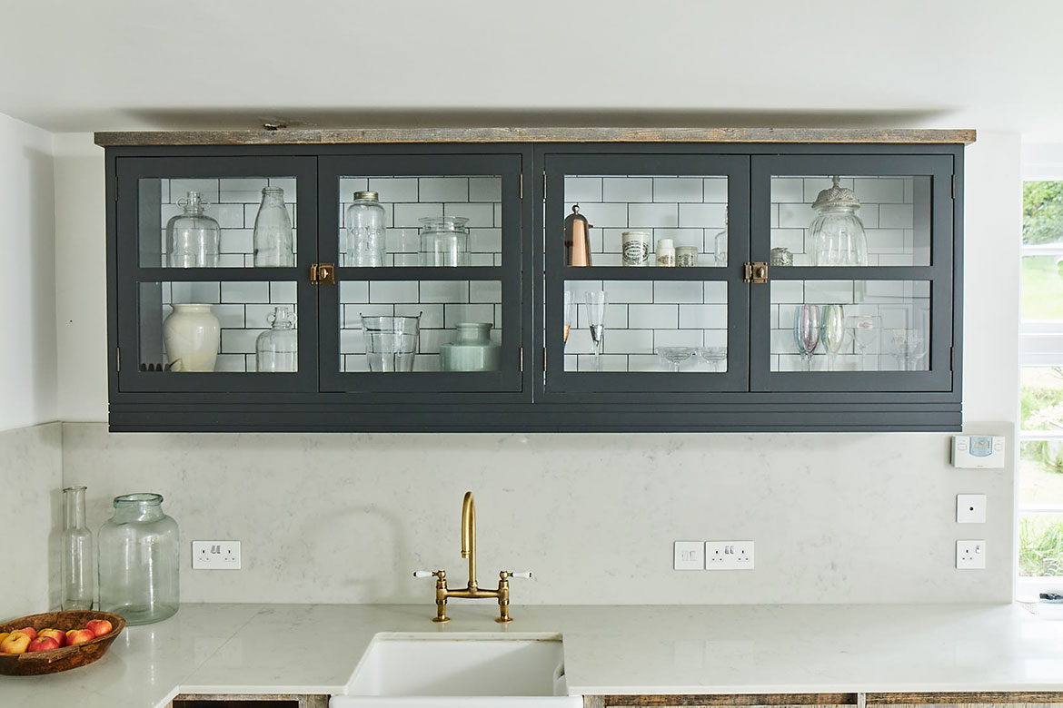 Pair of double door wall cabinets above ceramic sink with metro tiles