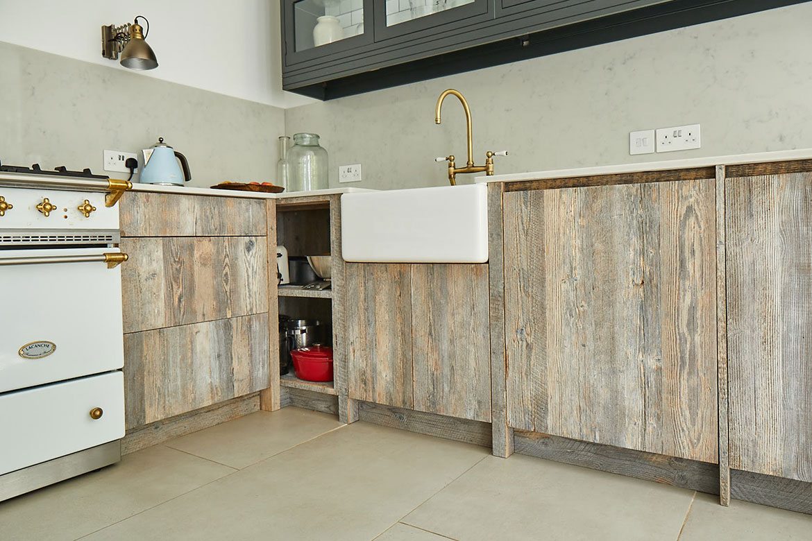 Ceramic Belfast sink with brass tap sits on bespoke reclaimed rustic cabinets with white quartz worktop and white range cooker