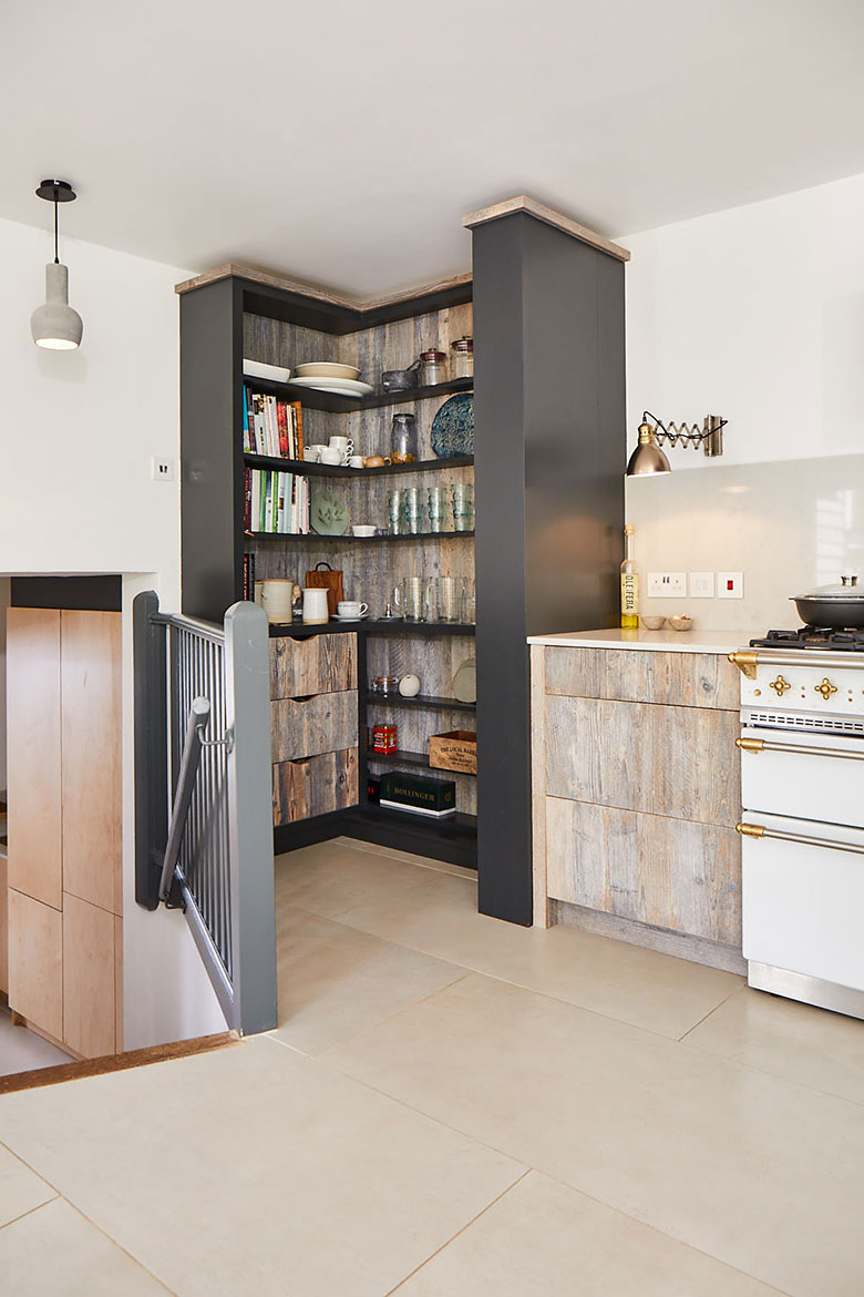 Tall open kitchen unit storing books glasses and mugs