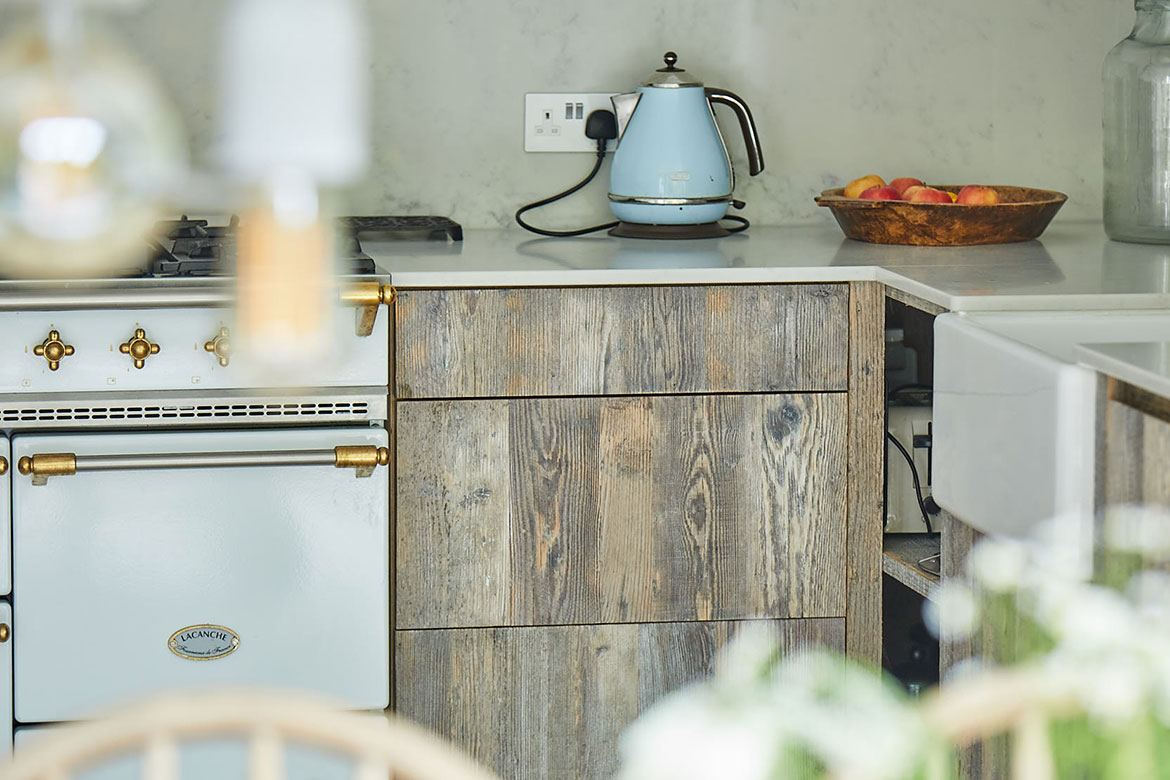 Light blue kettle sits on top of reclaimed rustic pine drawer stack