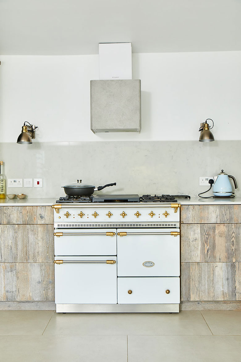 Classic white Macon range cooker by Lacanche with concrete canopy and driftwood kitchen cabinets