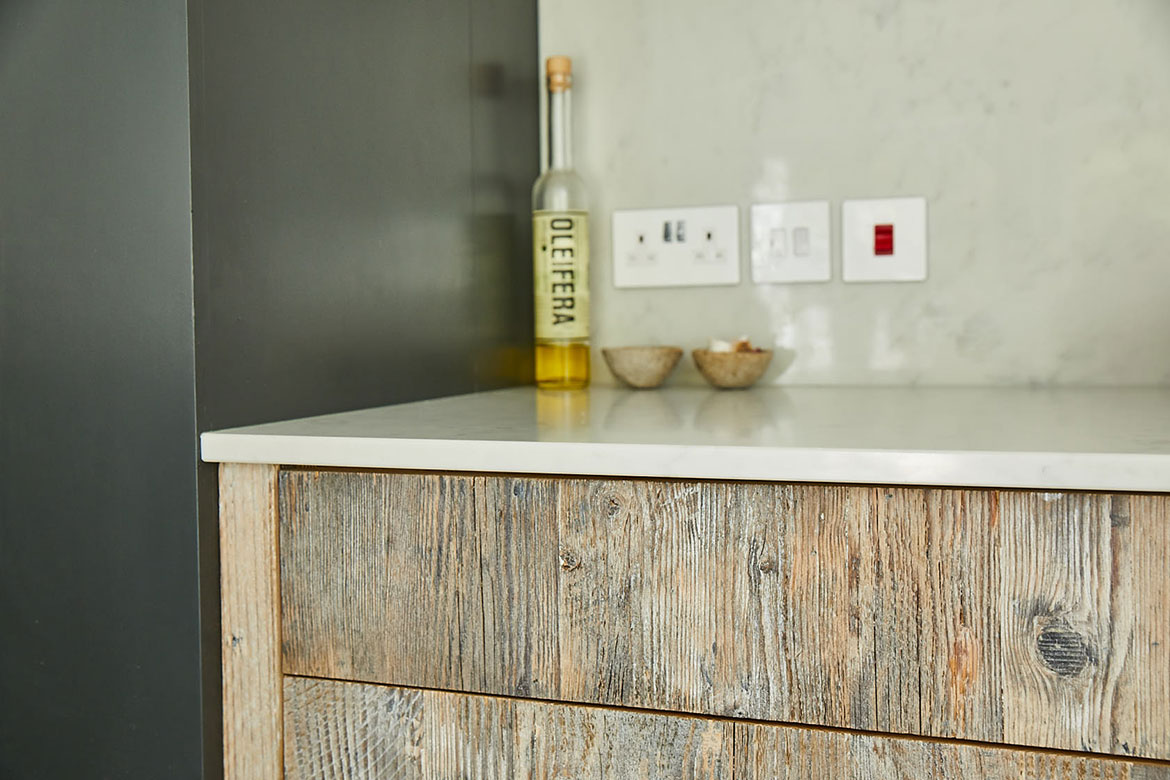 Engineered drawer fronts made from reclaimed rustic pine with white quartz worktop