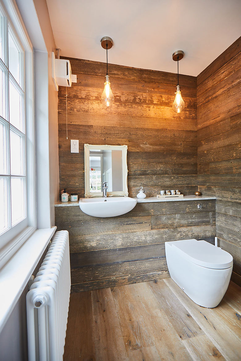 Wood cladded bathroom with floating sink and toilet