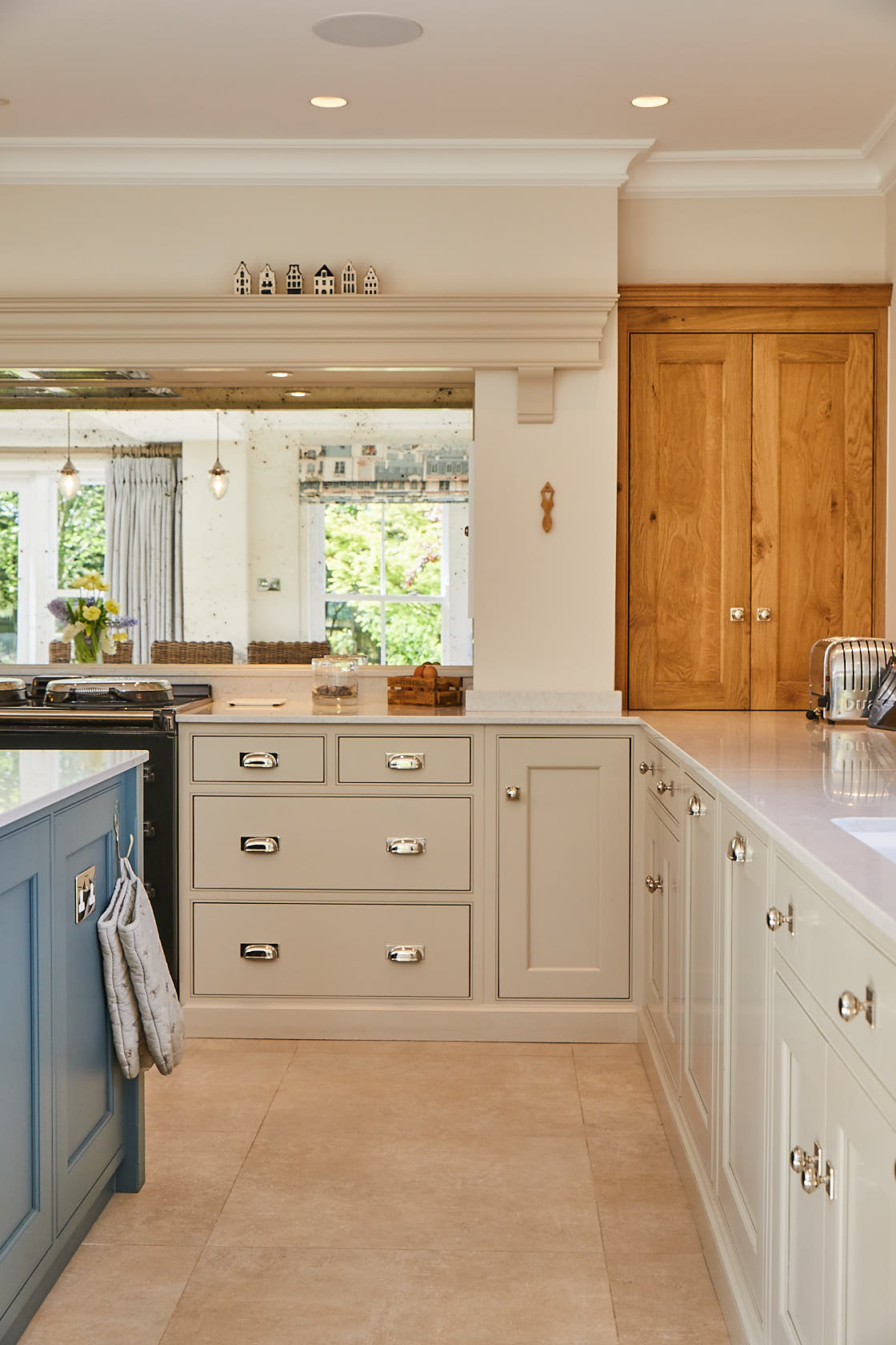 Painted cream kitchen cabinets contrast with solid oak traditional wall unit nestled in alcove