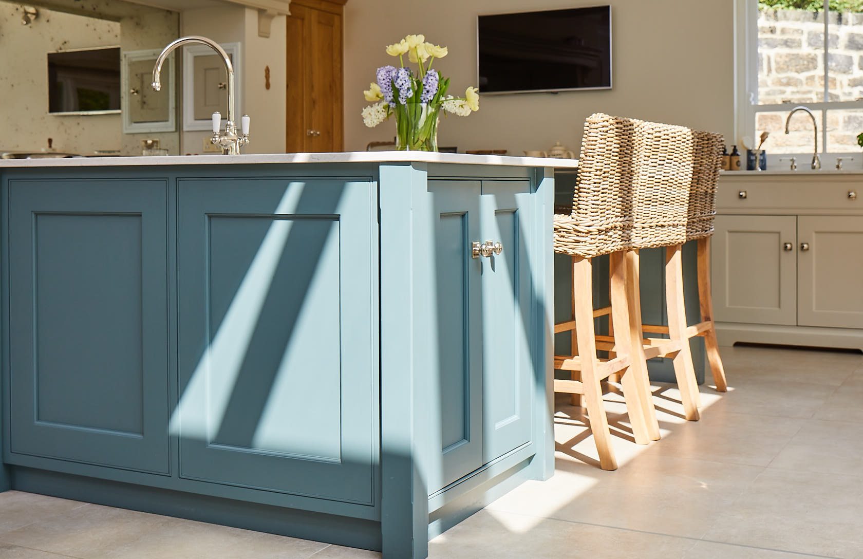 Sun shines on painted green kitchen island with wicker bar stools pushed under worktop