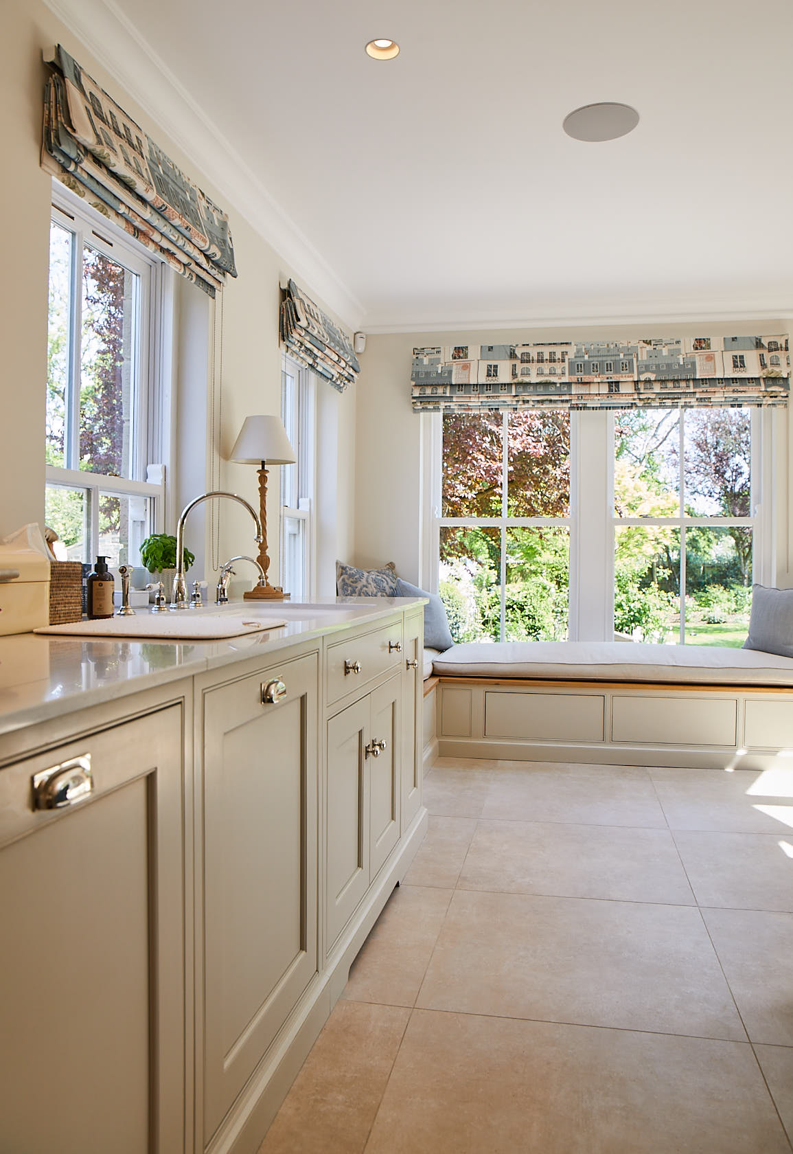 Traditional painted kitchen units with integrated ceramic sink and window seat