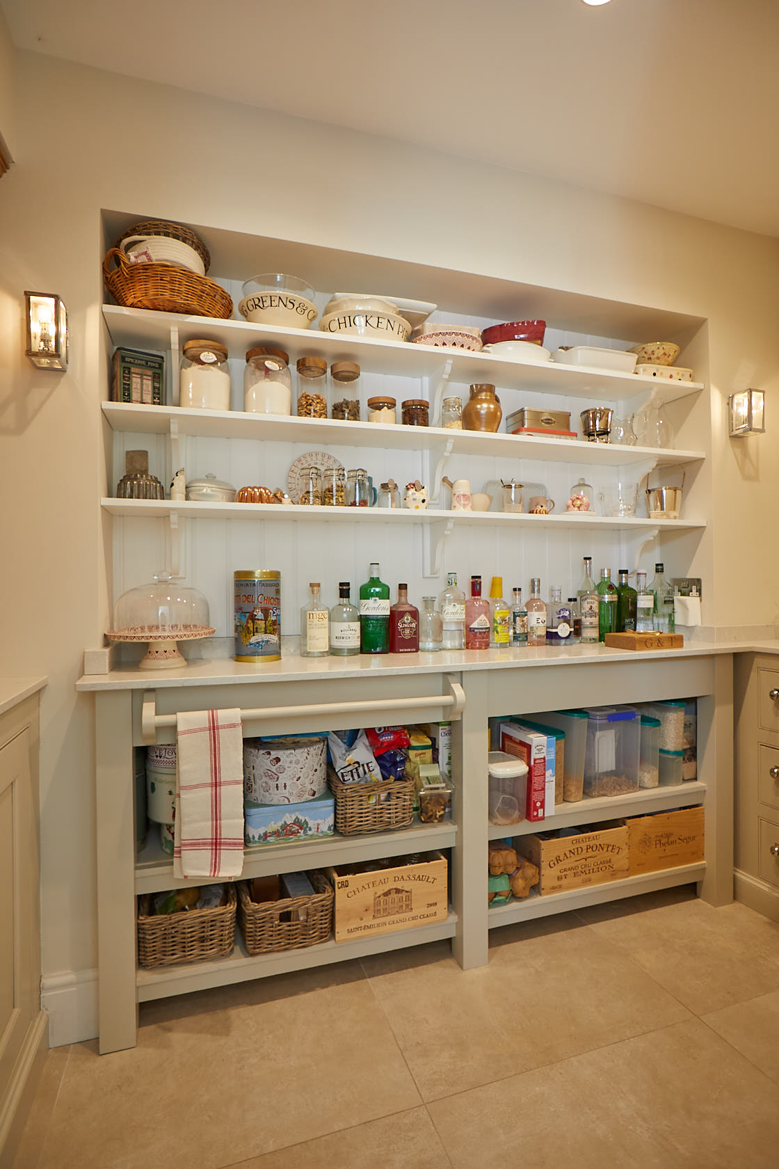 Pantry food storage on bespoke cream pained open shelves and pot board with white quartz top