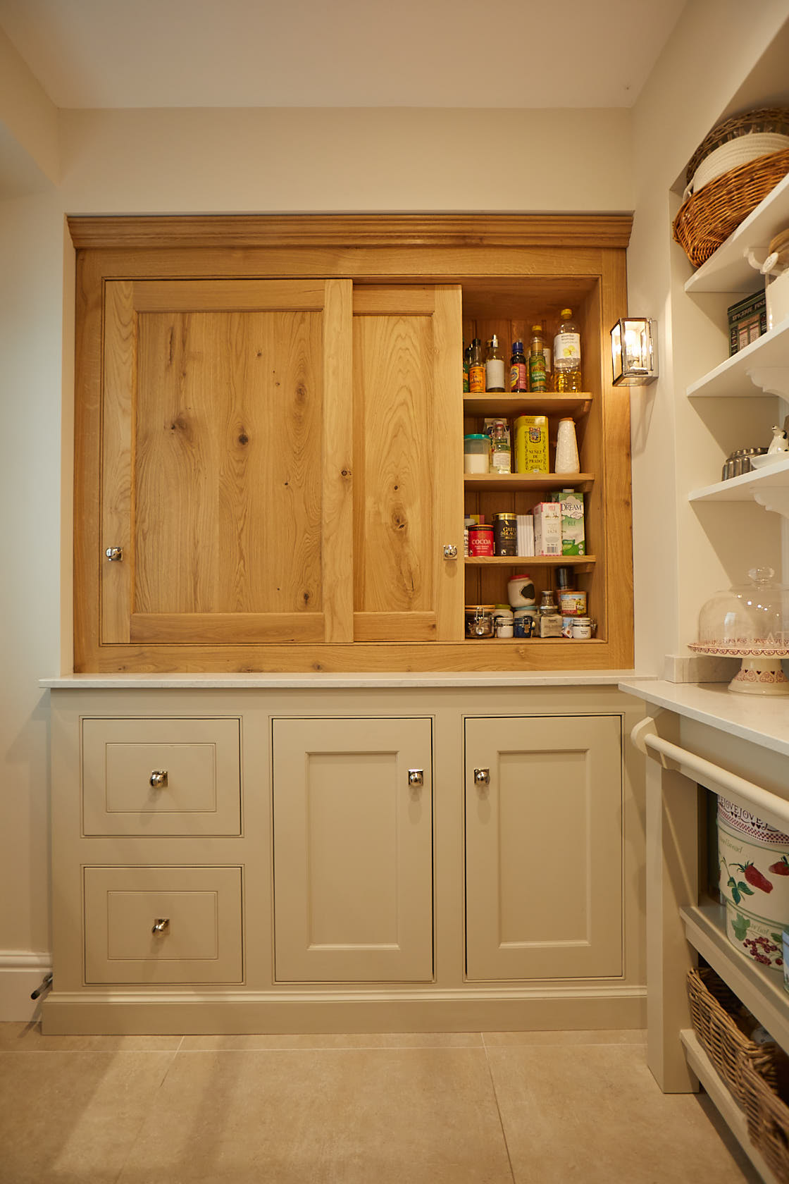Sliding oak shaker doors in pantry with painted cream base cabinets