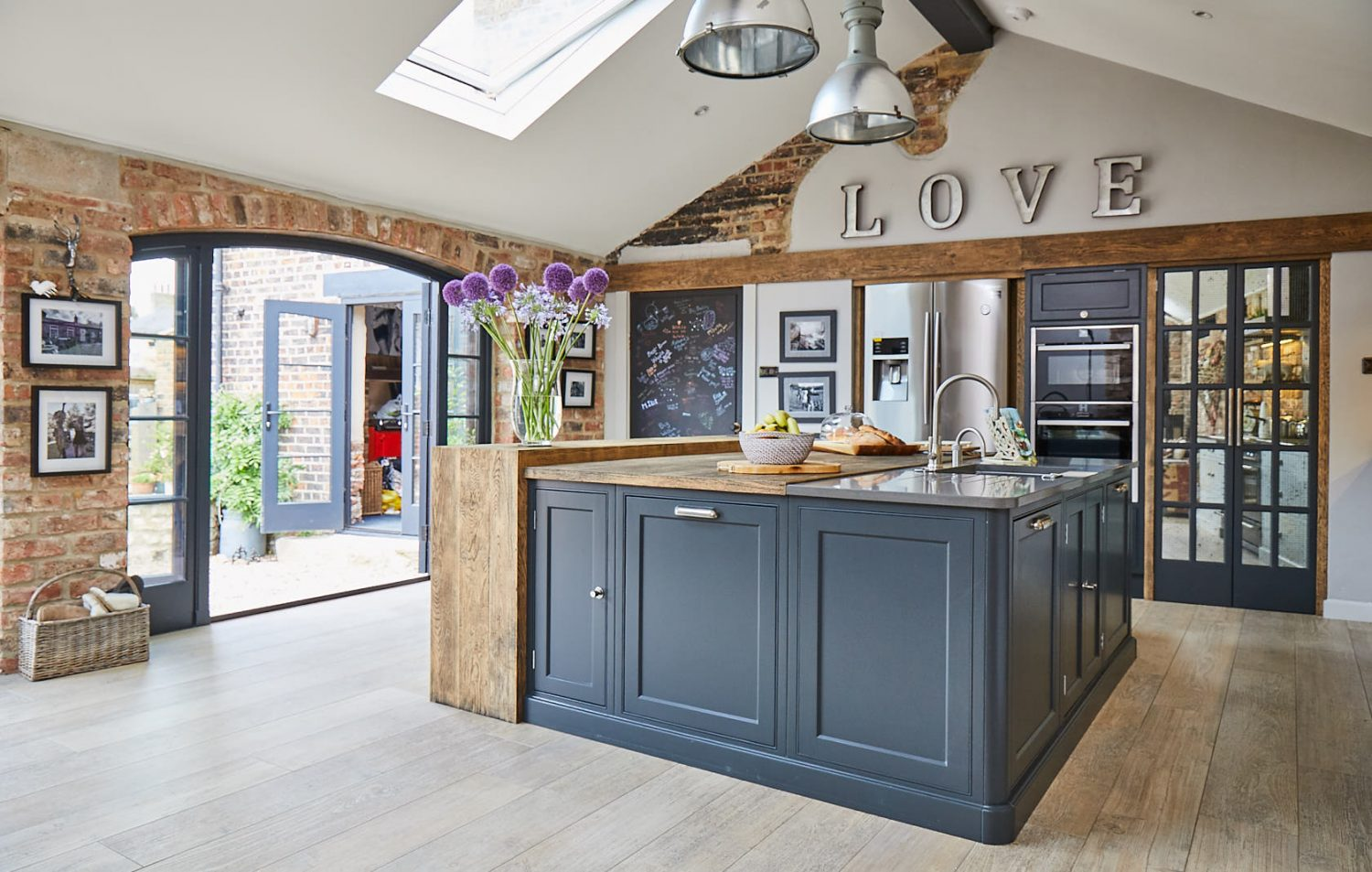 Painted Lamp Black shaker cabinets make up kitchen island with Caesarstone and oak worktop