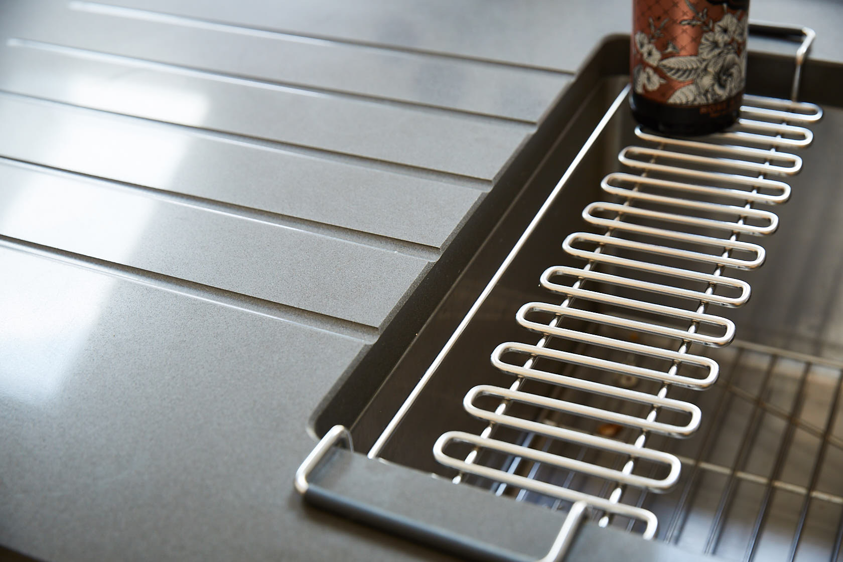 Caesarstone worktop with drainage grooves and wire rack above stainless steel metal sink