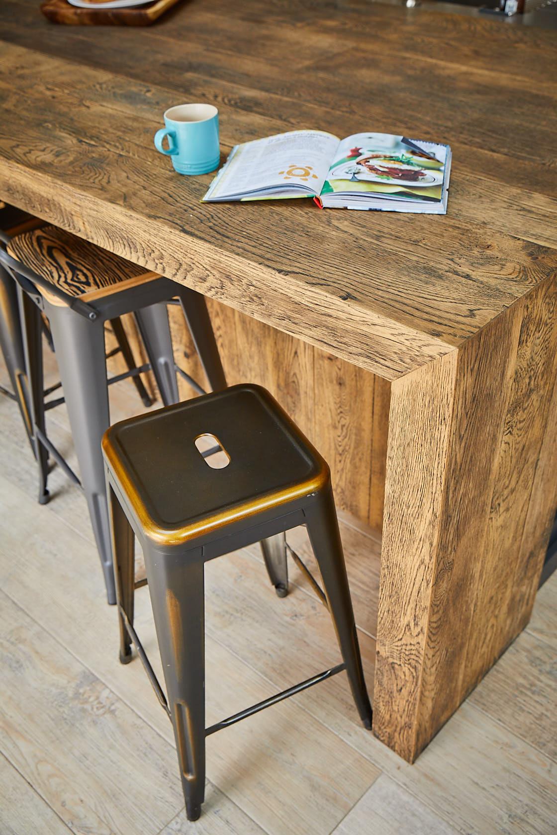 Industrial metal bar stool next to hand aged oak breakfast bar