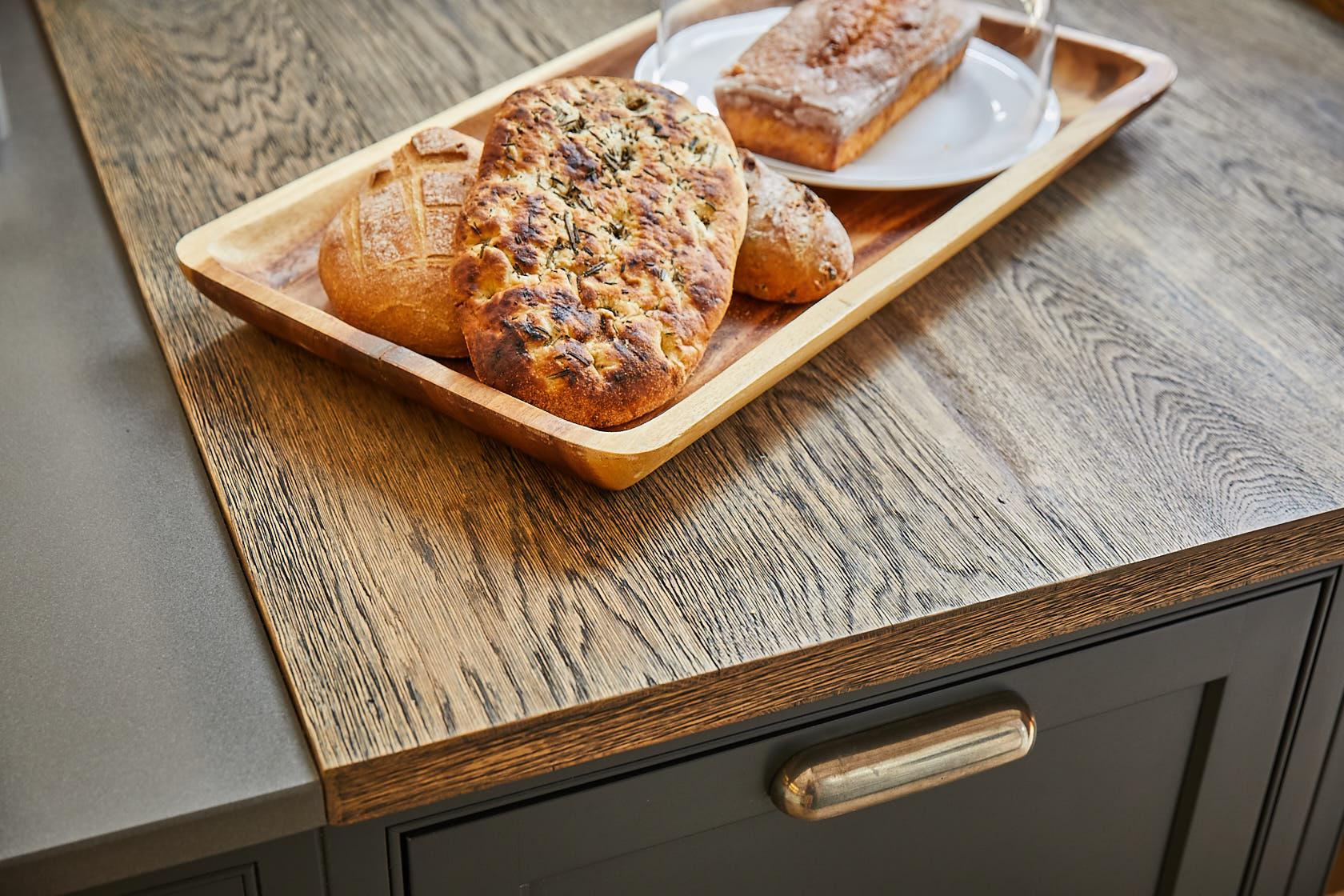 Fresh bread sits on engineered rustic oak wood worktop