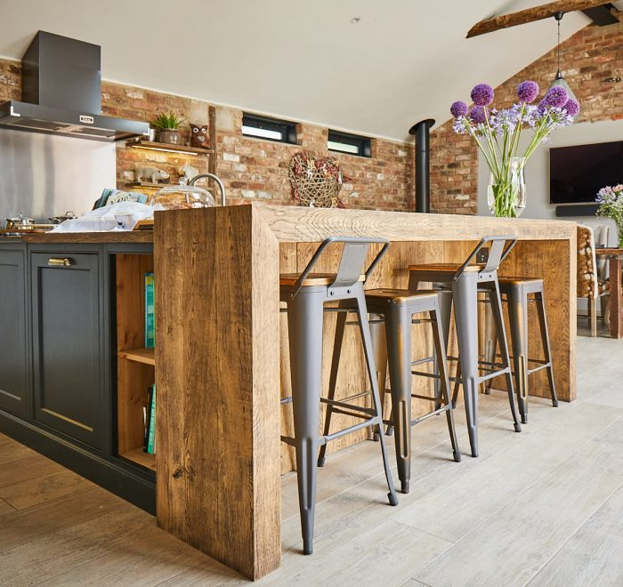 Open unit next to oak chunky breakfast bar and industrial metal bar stools