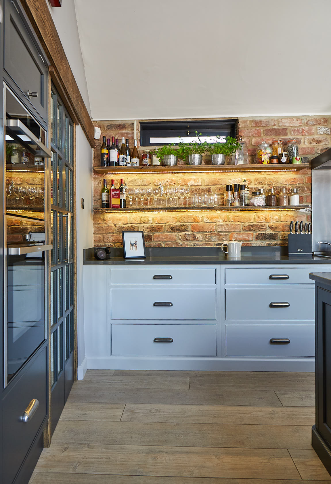 Light grey pan drawers below exposed brick wall with open rustic oak shelves above