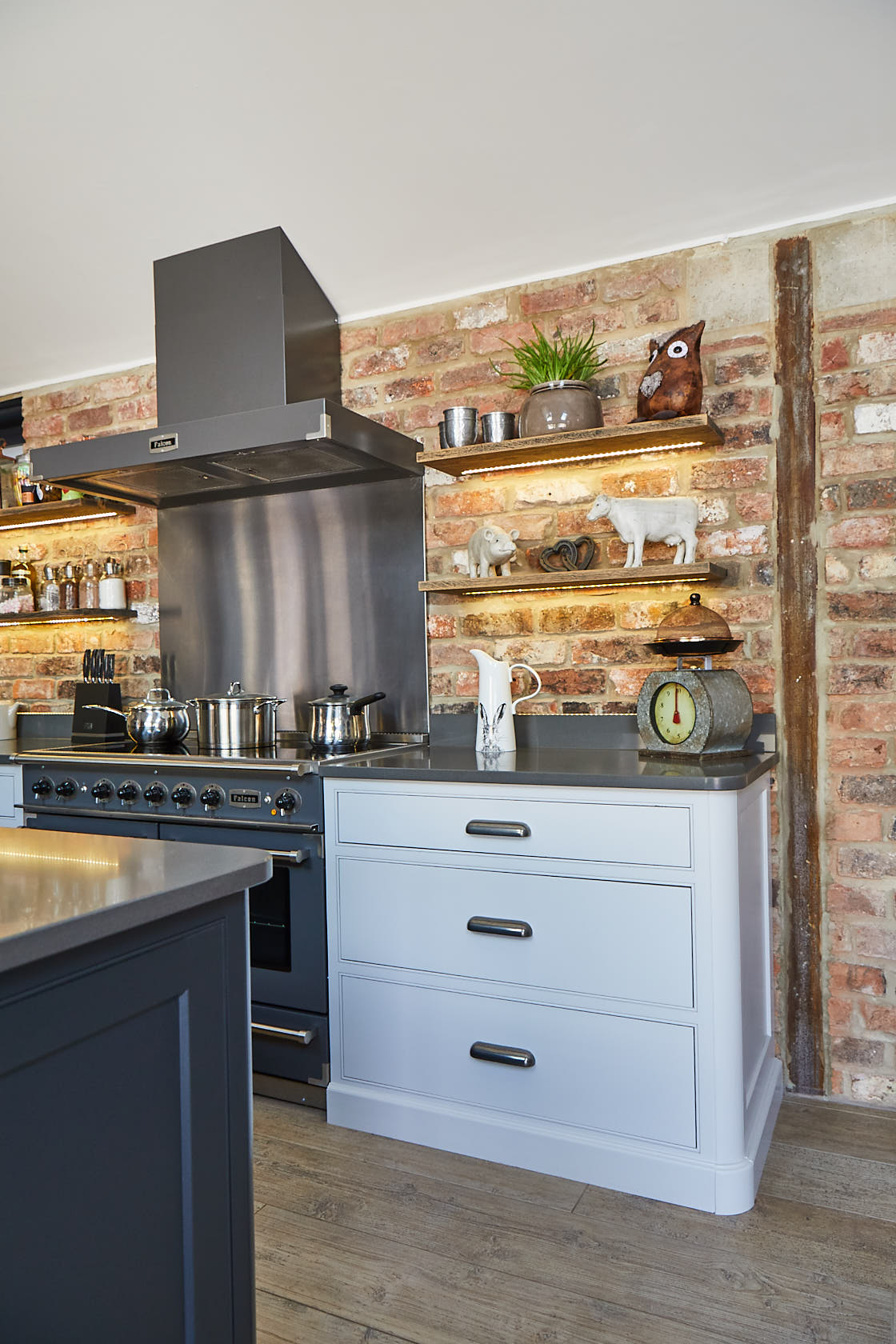 Grey range cooker with stainless steel extractor against exposed brick wall