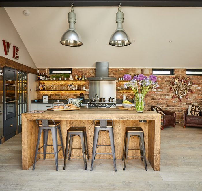 Large reclaimed pig lamps shine on engineered oak hand aged breakfast bar and stools