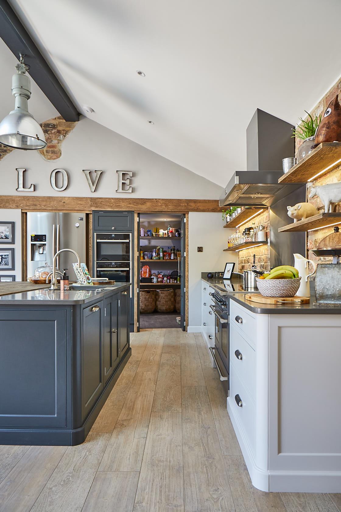 Hidden pantry room behind kitchen cabinet doors and rustic oak wood trim