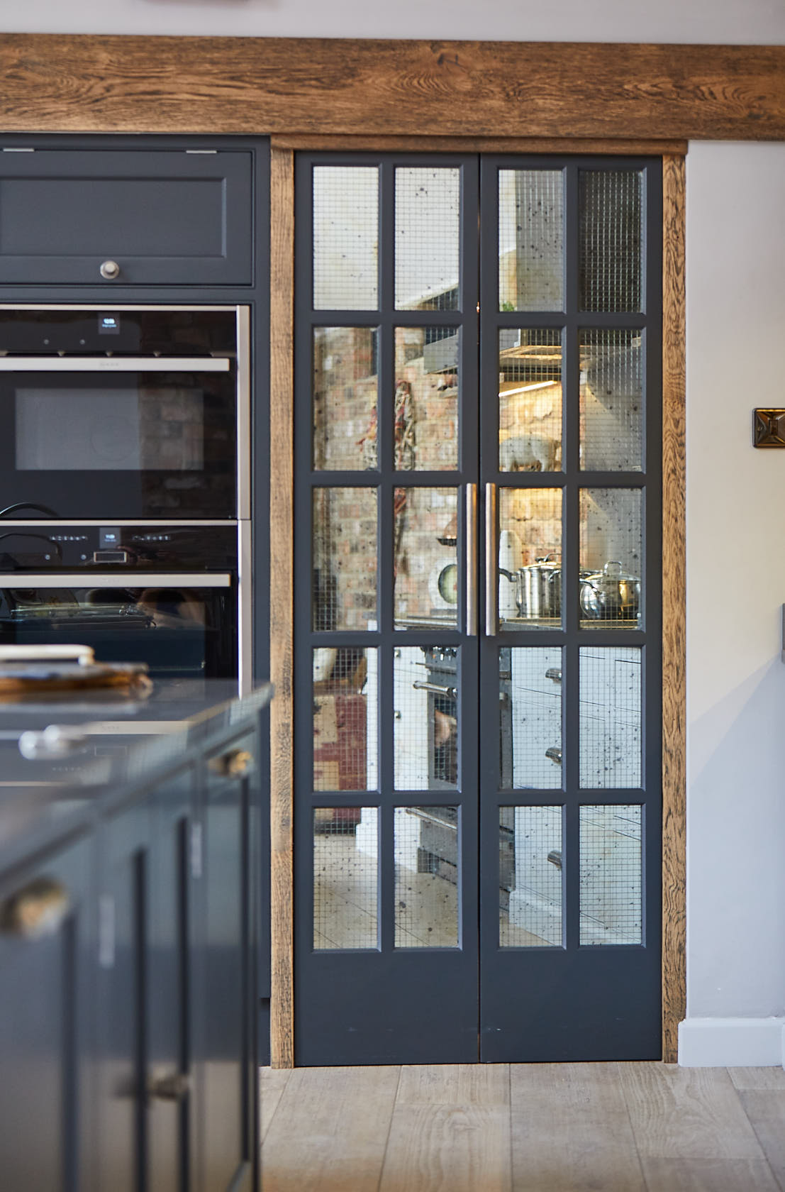 Pair of bespoke pantry doors with Rough Old Glass mirror and rustic wood surround