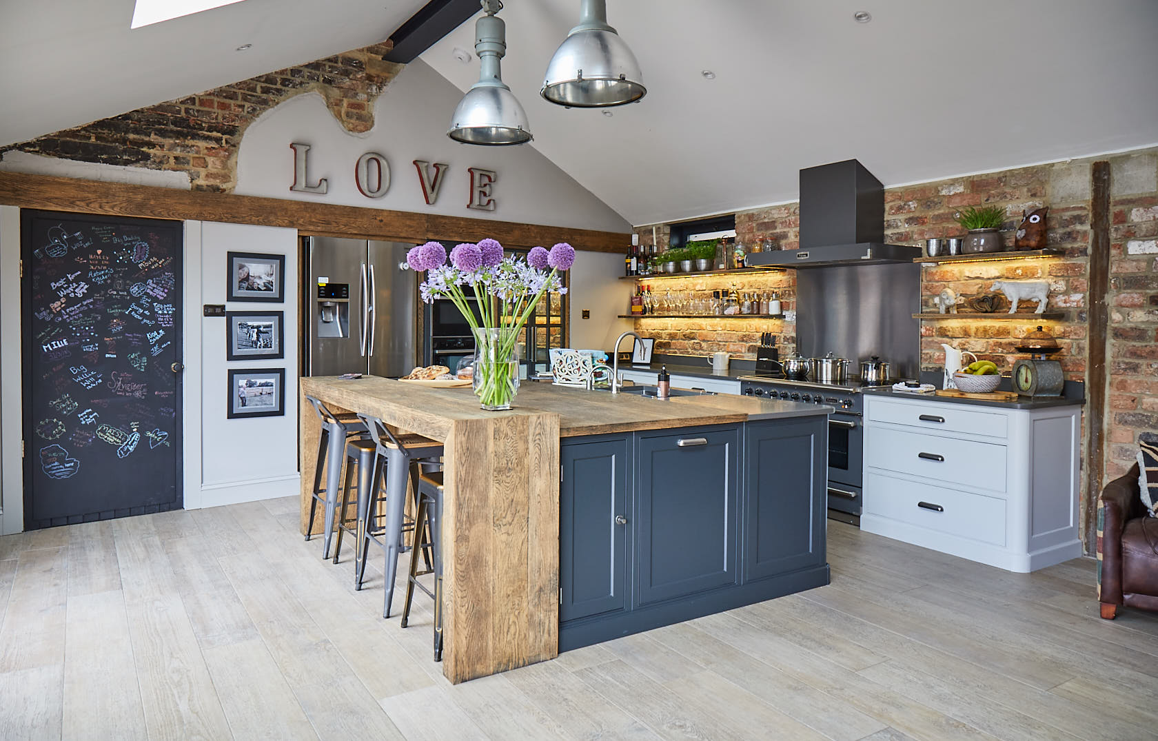 Flowers sit on large bespoke kitchen island with rustic oak breakfast bar and lamp black painted cabinets