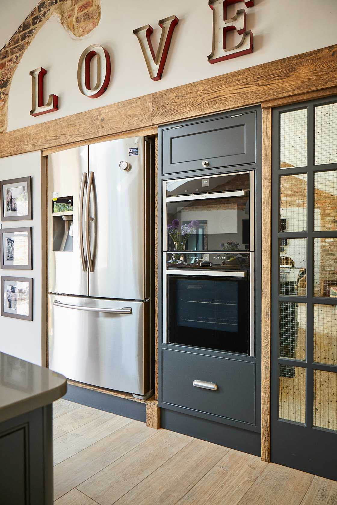 Double over and stainless steel fridge flush with wall in bespoke kitchen design