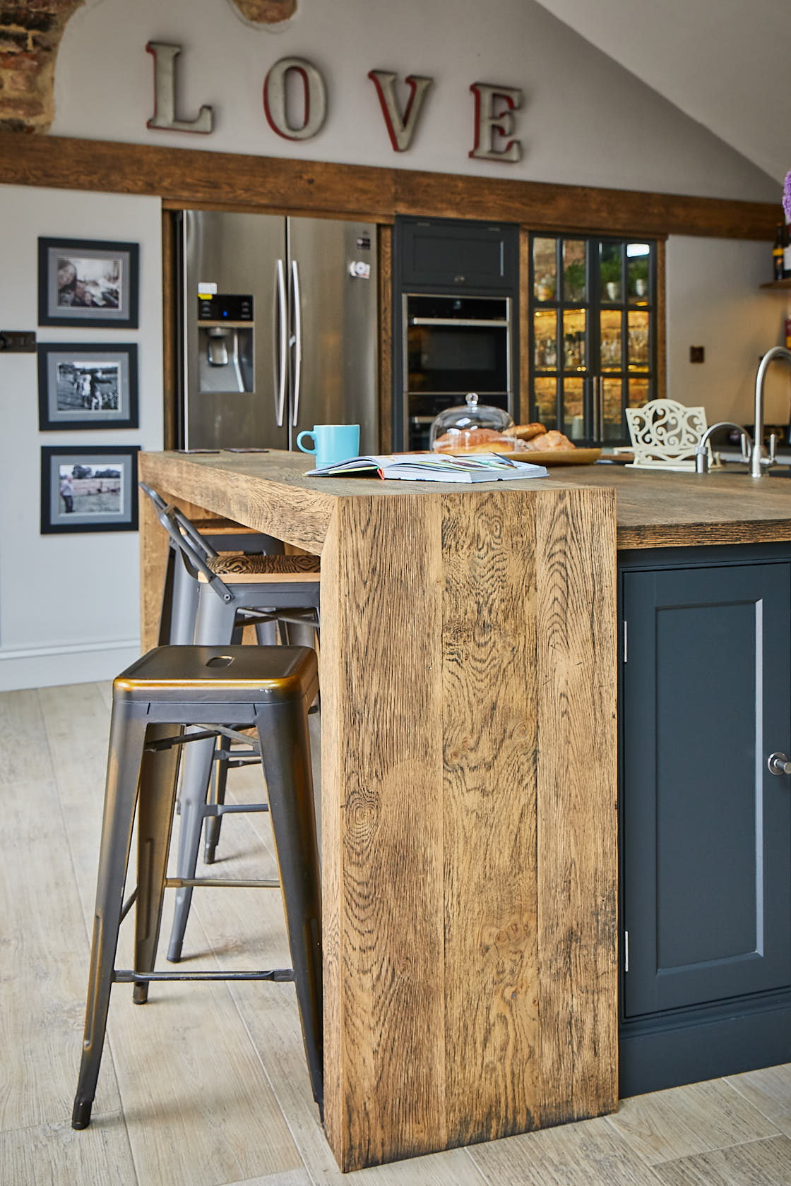 Wrap around chunky oak breakfast bar with industrial metal bar stool
