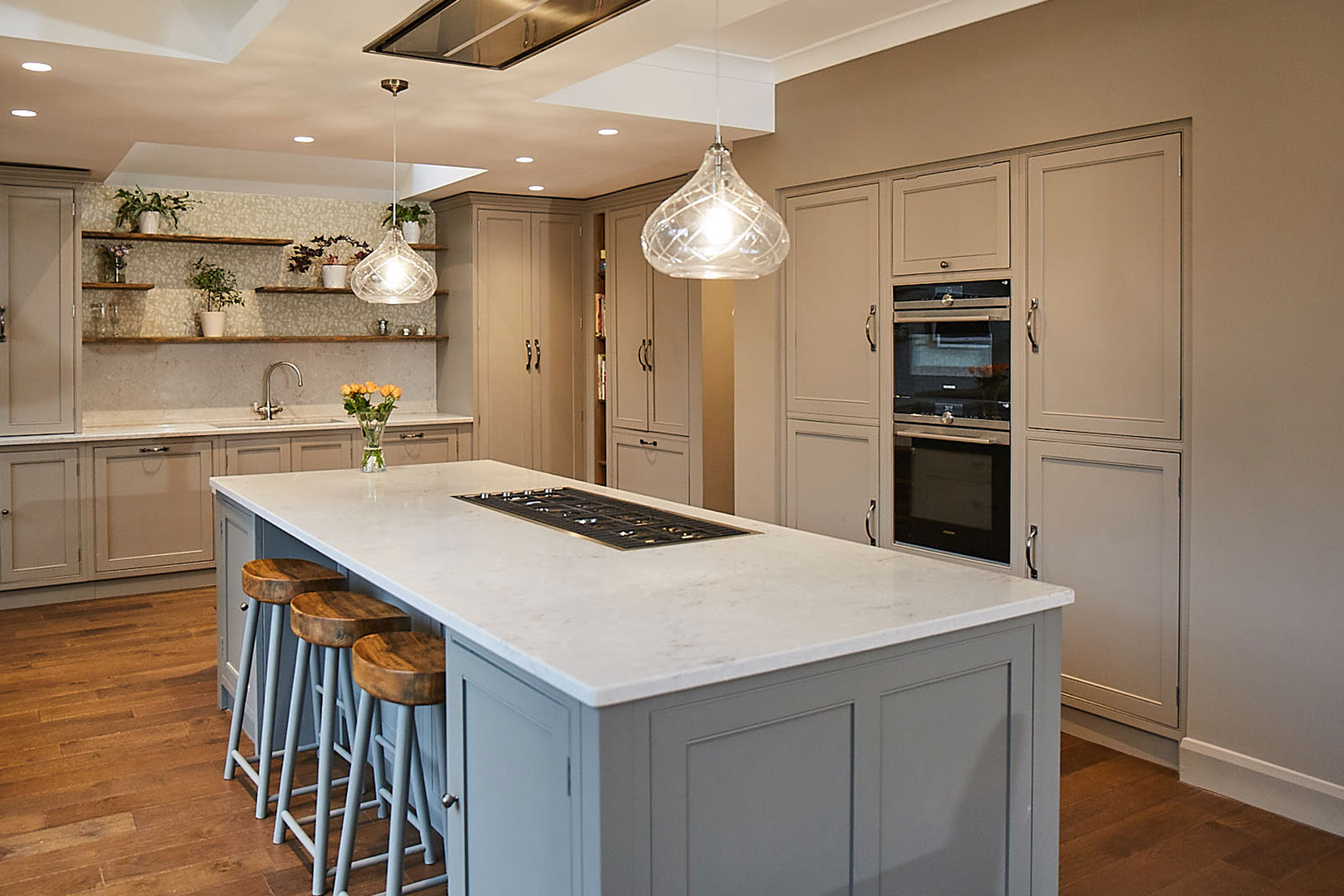 Crystal pendant lights above traditional painted kitchen island with white quartz worktop