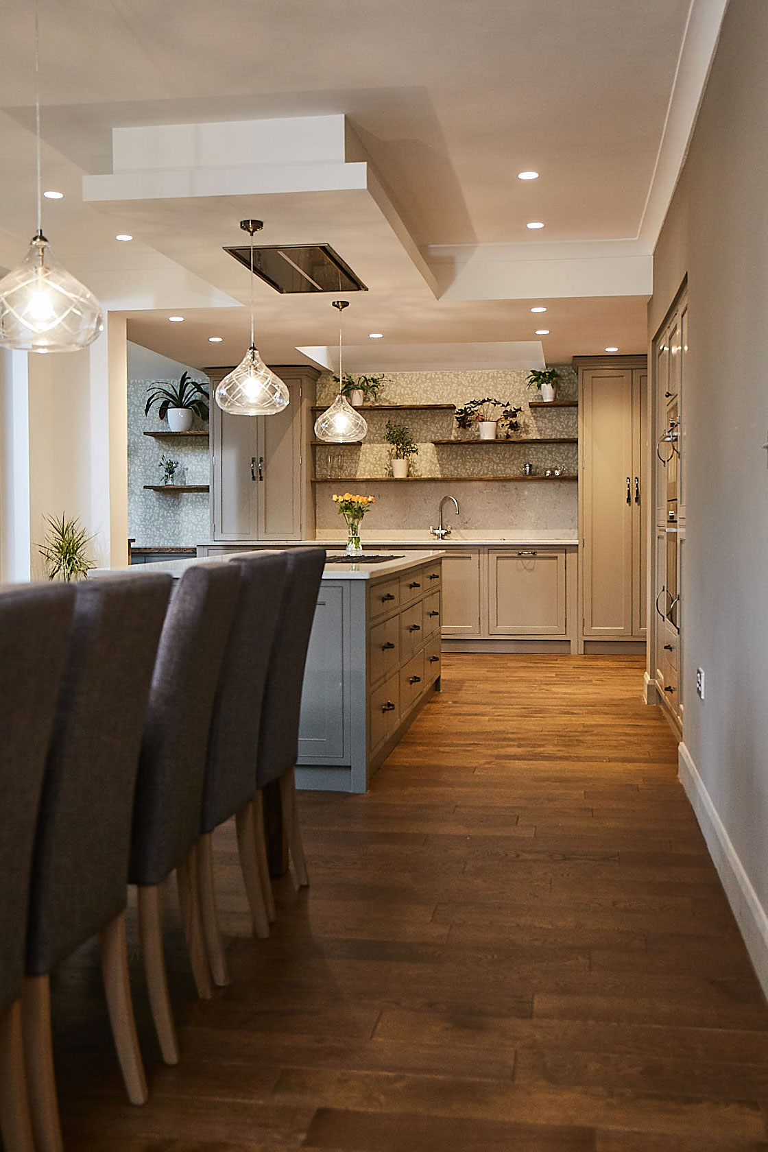 Upholstered chairs in open plan bespoke painted kitchen
