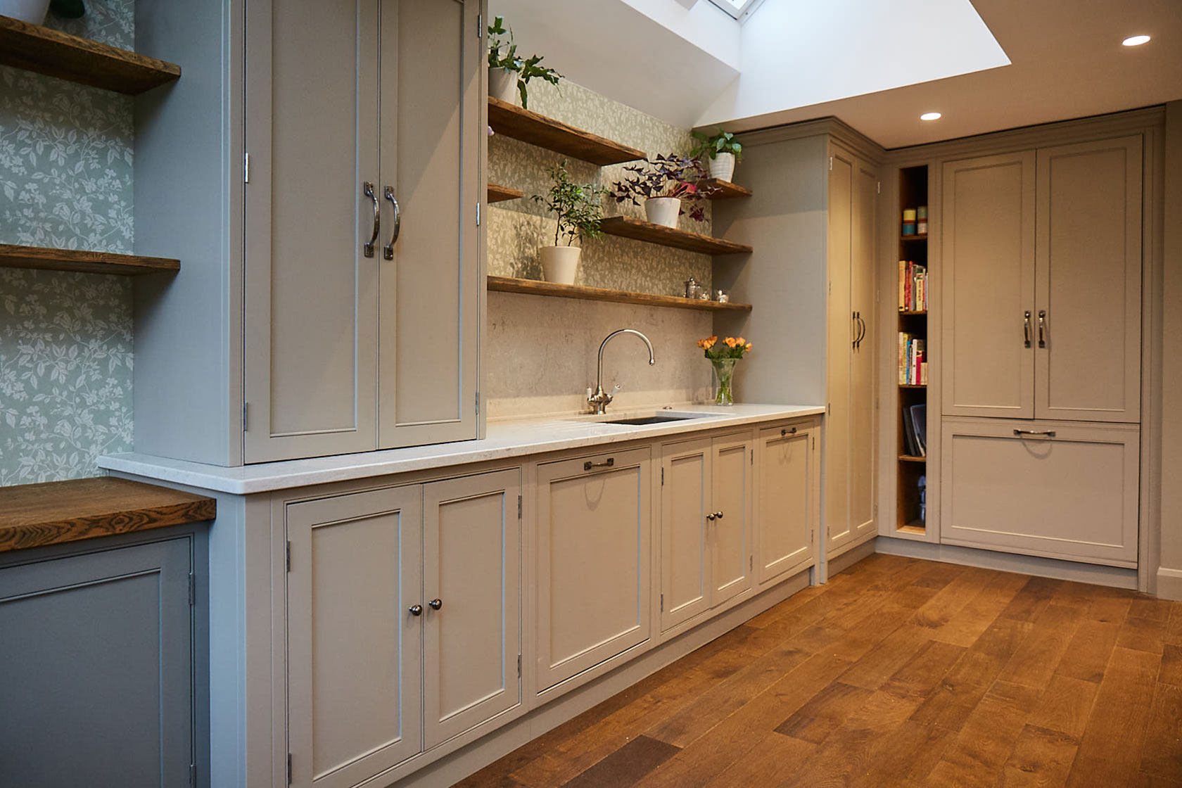 Sink run with asymmetrical oak open shelves above