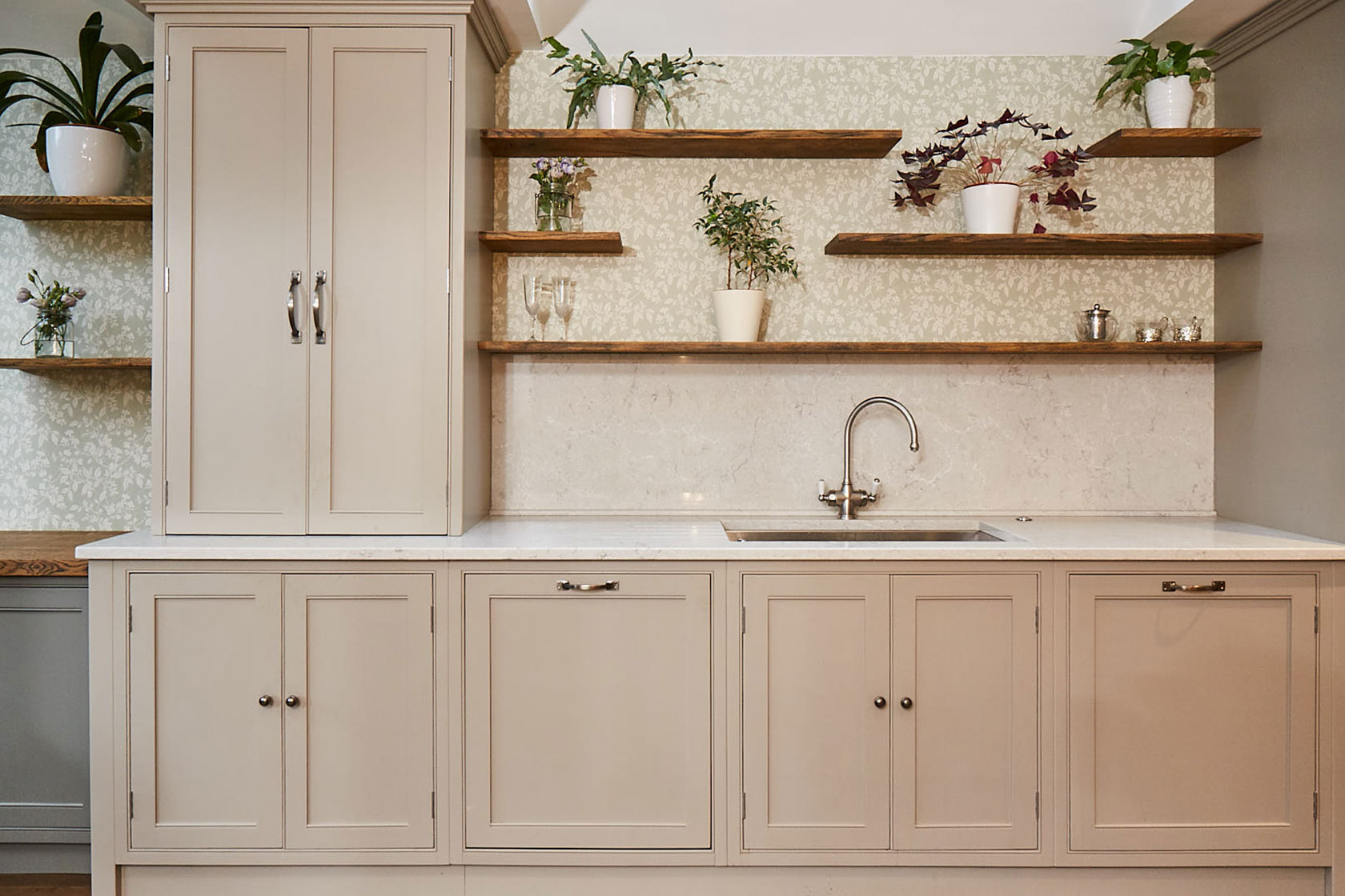 Traditional kitchen sink run with open oak shelves and green wallpaper