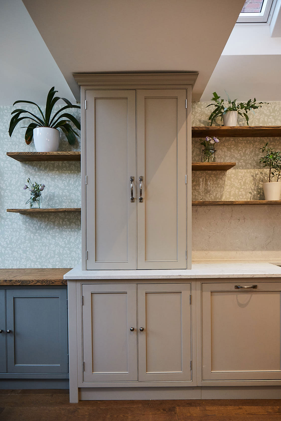 Wall unit sits on white worktop with open wood shelves left and right