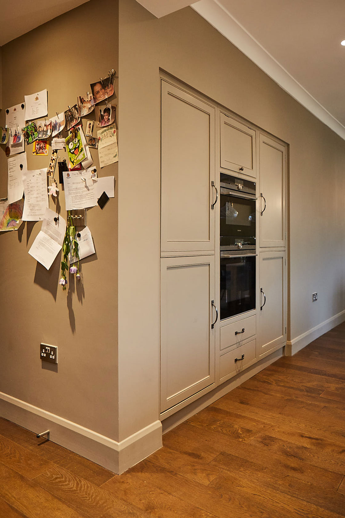 Notes stuck on wall next to integrated tall kitchen units and double oven by Siemens
