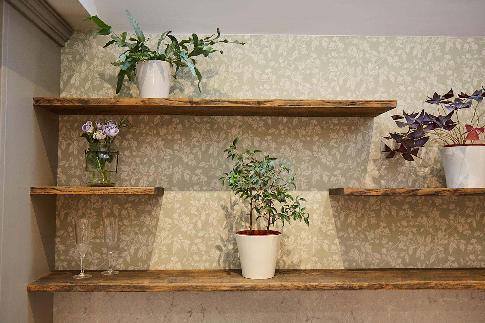 Plants sat on floating oak wood shelves with green floral back drop