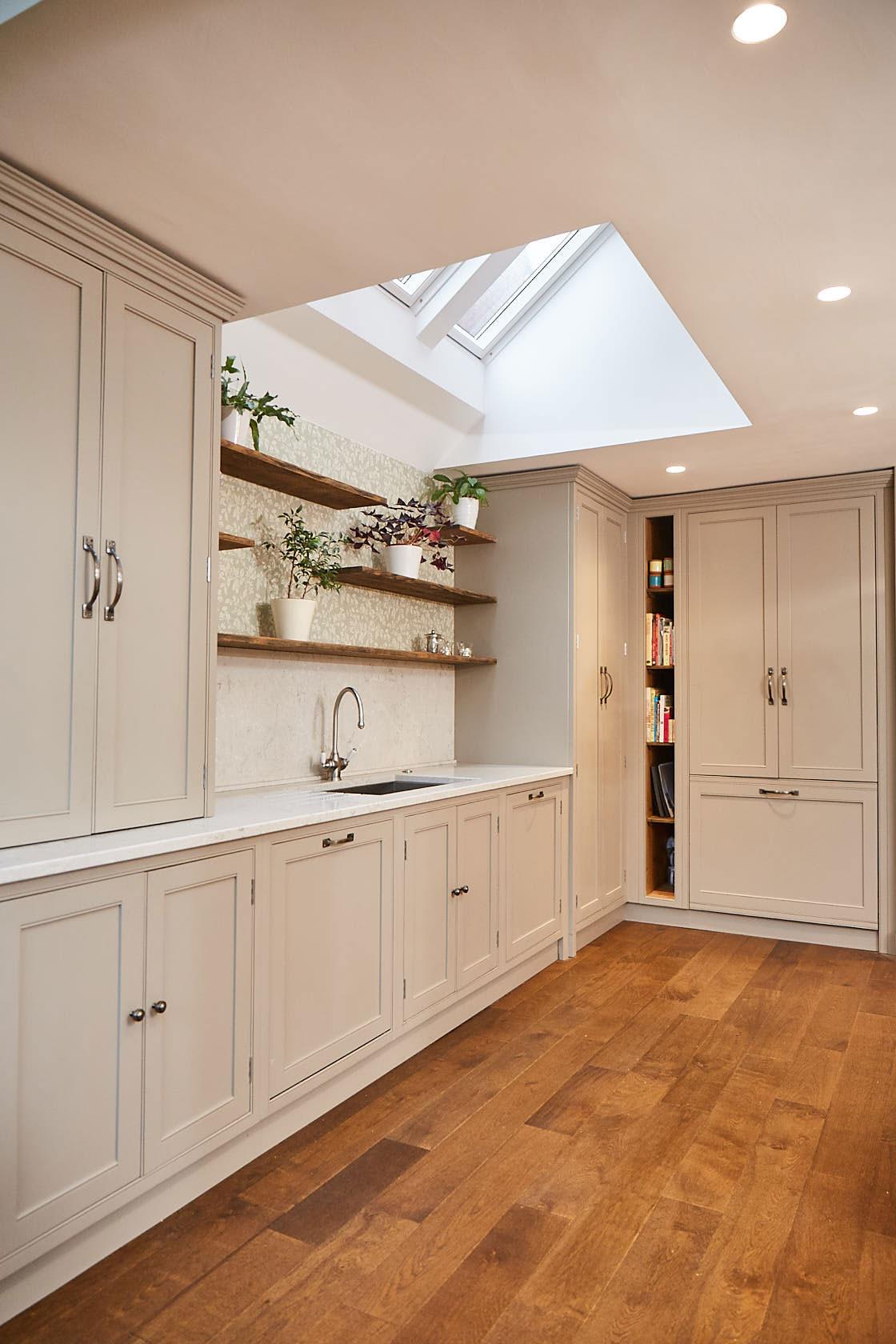 Reclaimed oak open shelves with plants above kitchen sink run