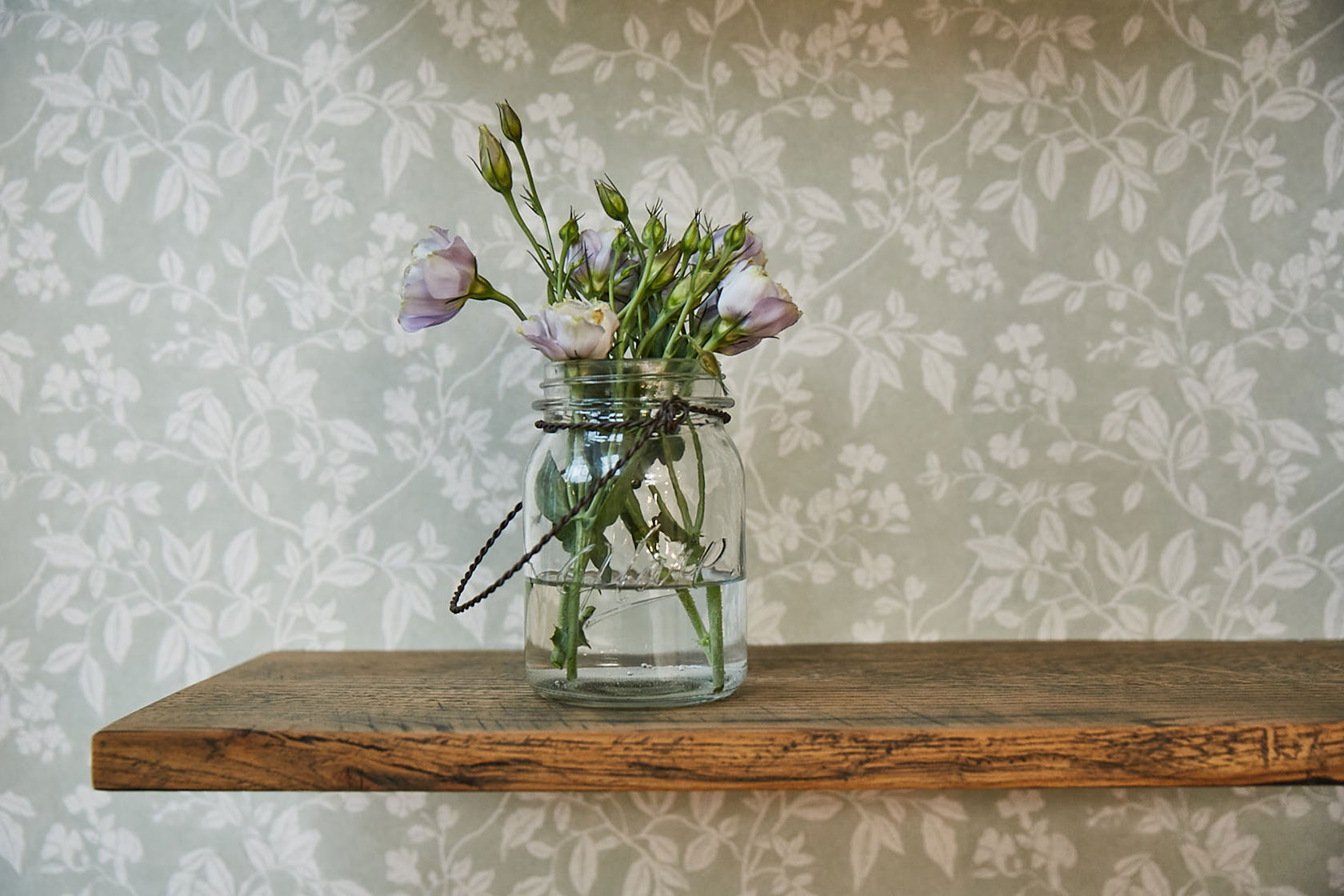 Flowers in glass jar sit on rustic oak shelf with green floral wallpaper background
