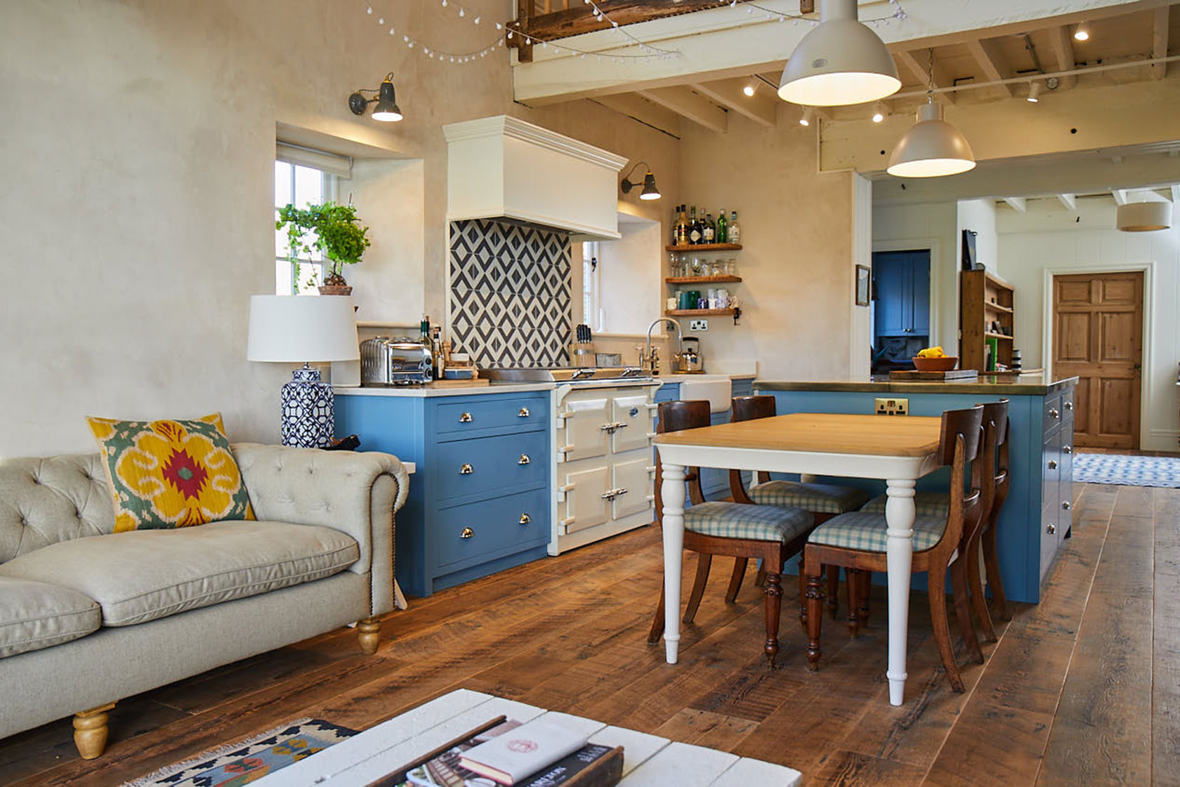 Open plan light blue kitchen with farmhouse table and cream sofa