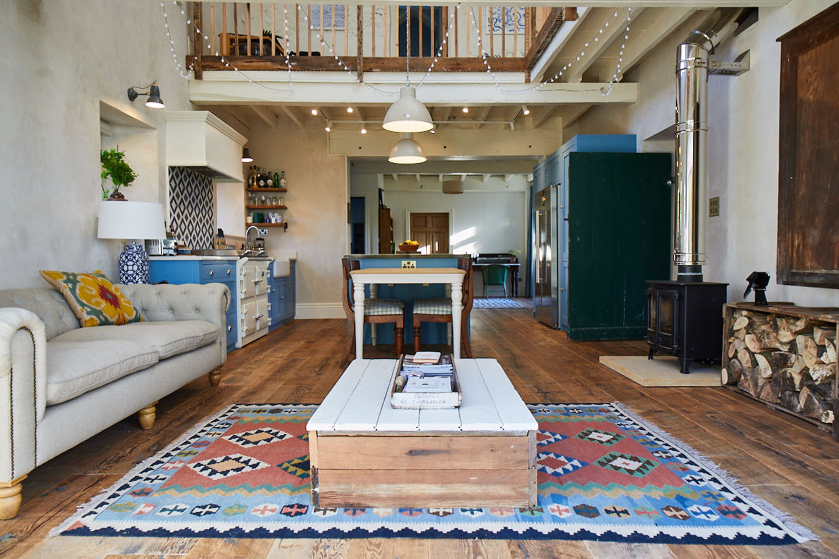 Reclaimed coffee table sits on large aztec rug with cream upholstered sofa