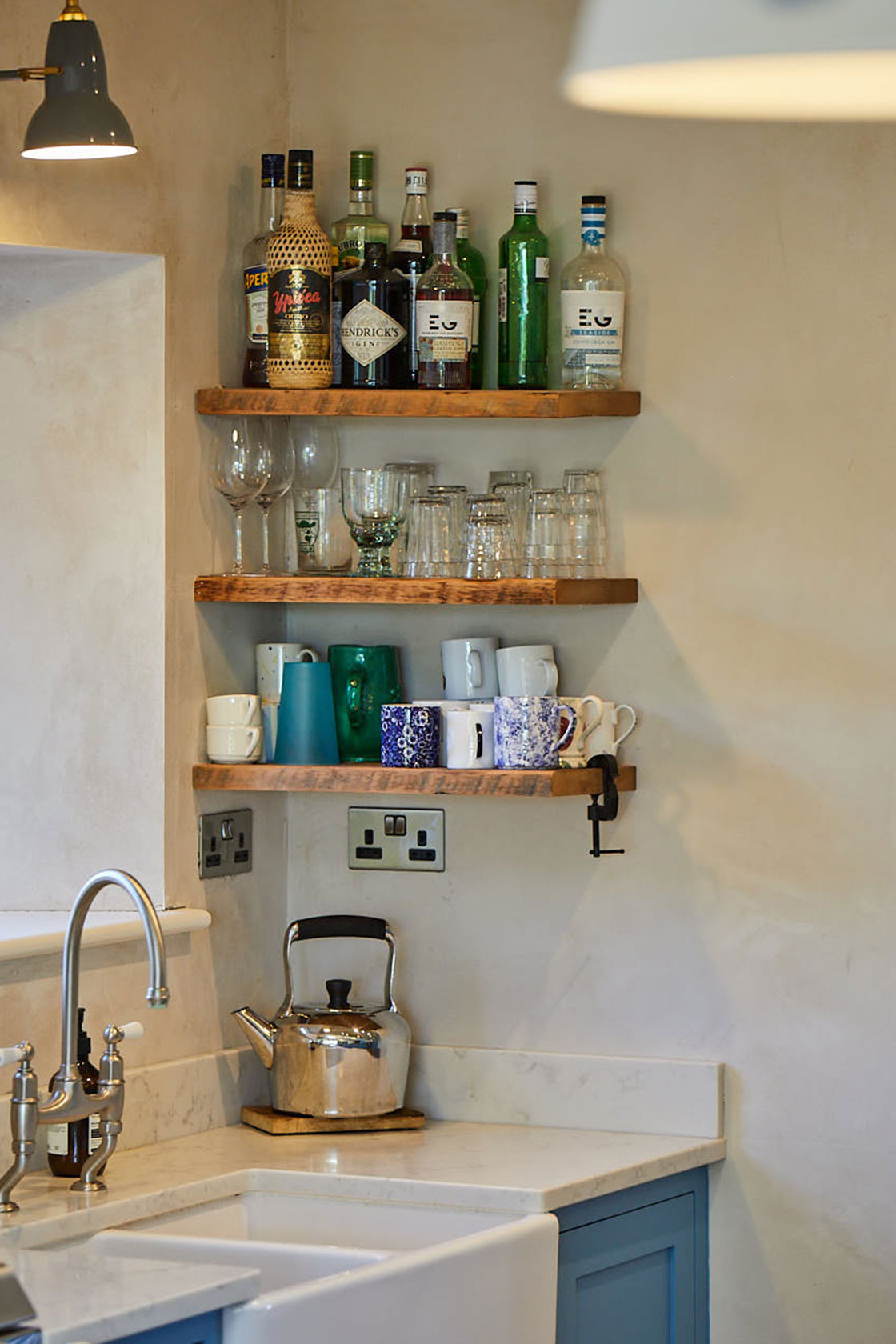 Spirits and condiments sit on reclaimed oak floating shelves