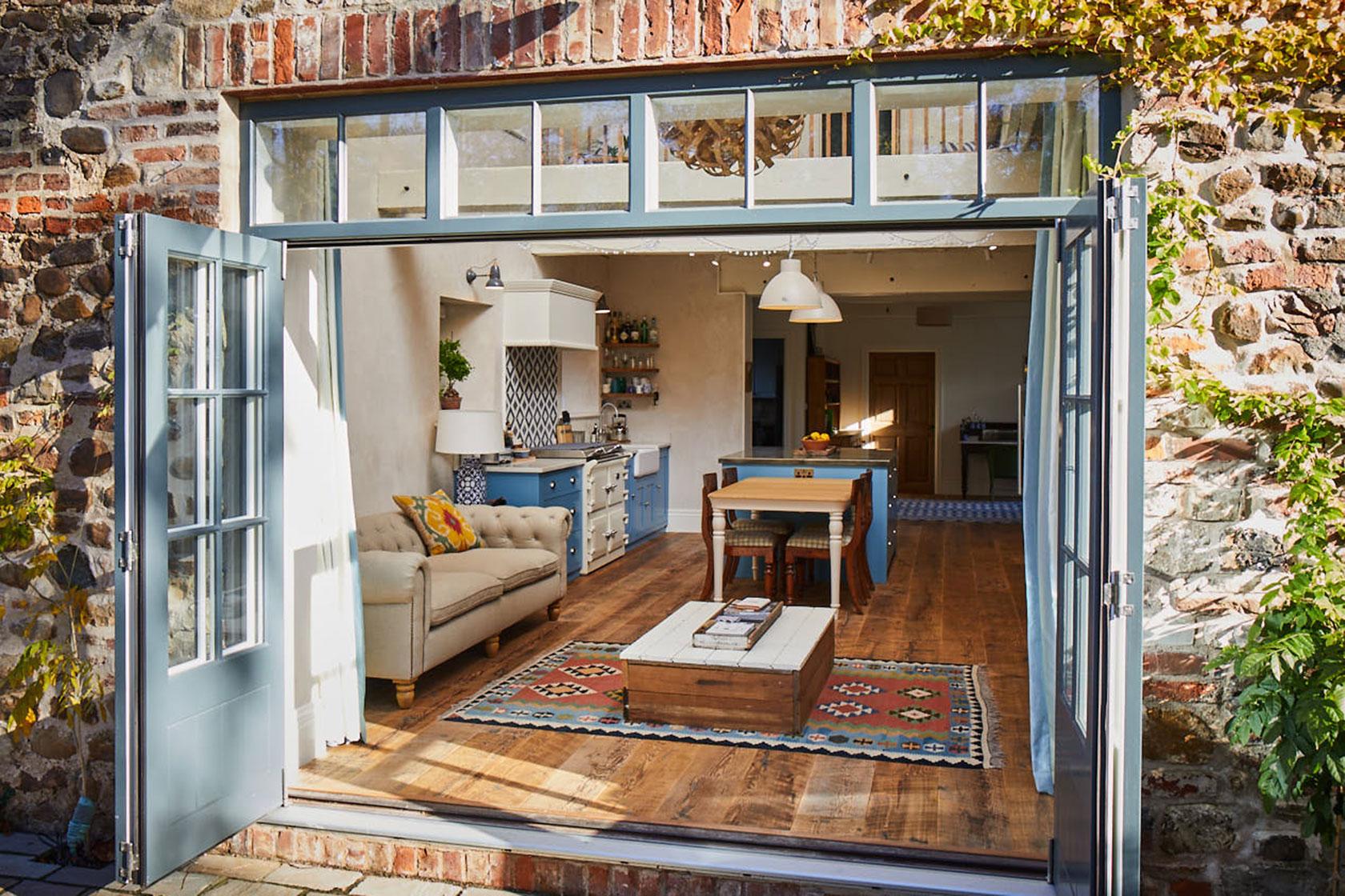 Patio doors lead to open plan kitchen with reclaimed pine floor