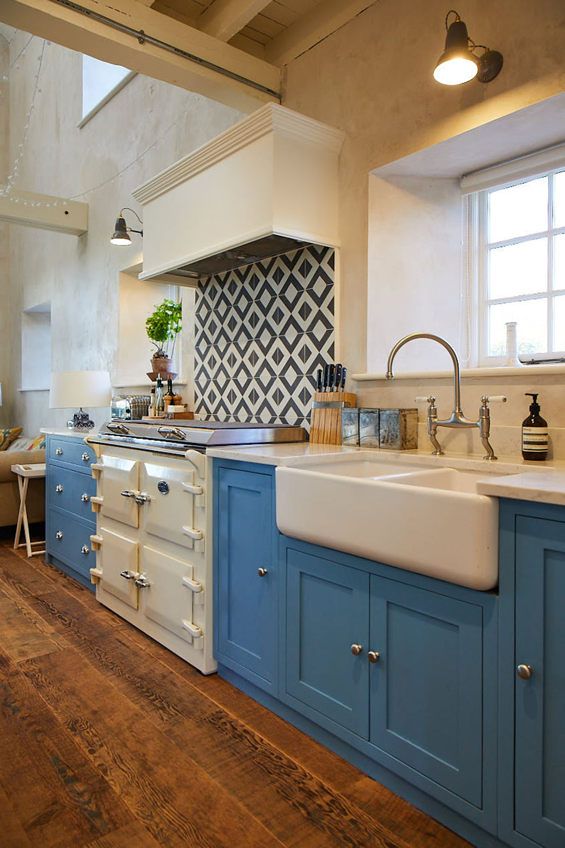 Cream Everhot cooker next to light blue kitchen cabinets and ceramic white double Belfast sink