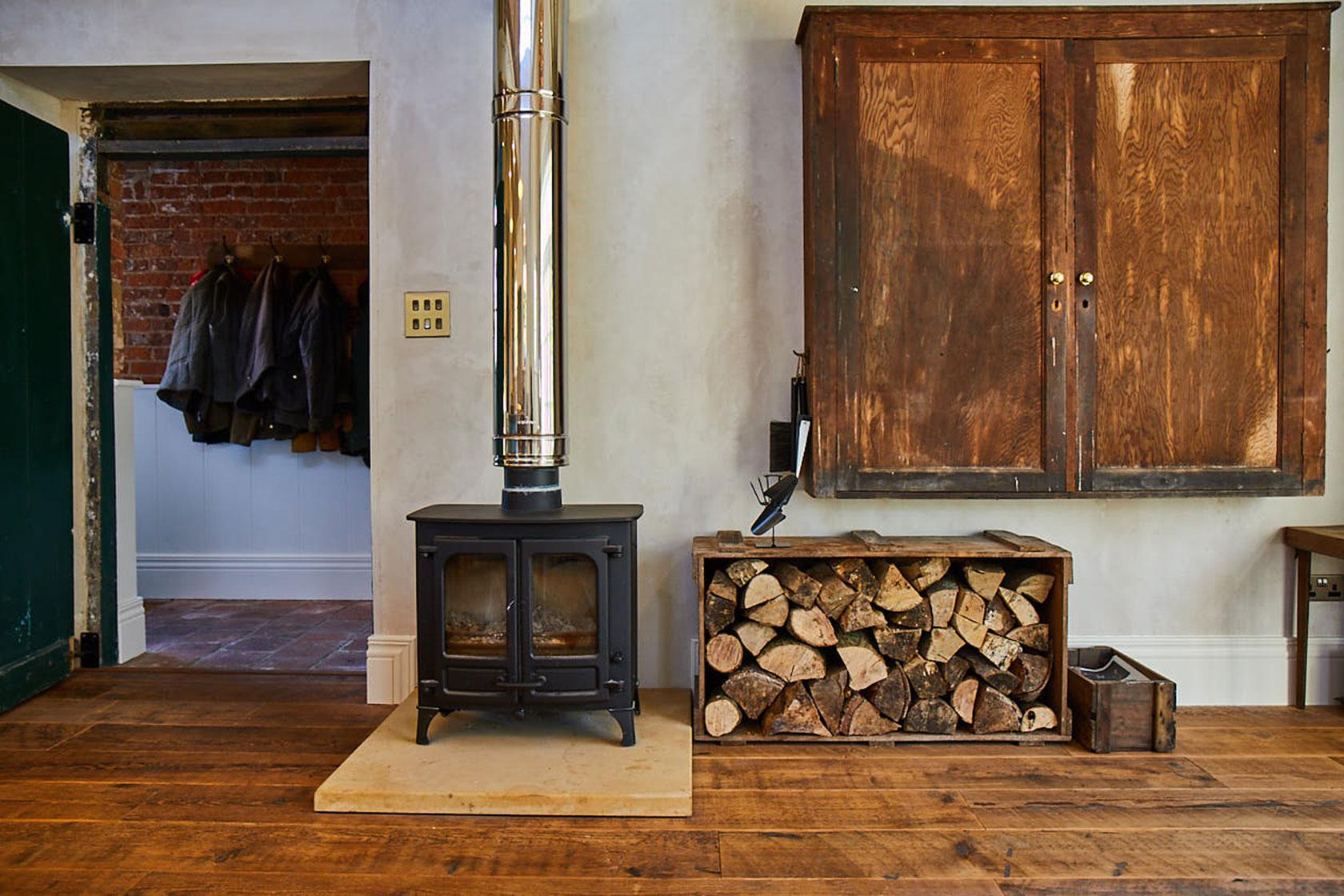 Rustic log burner sits on reclaimed floorboards with logs in log basket