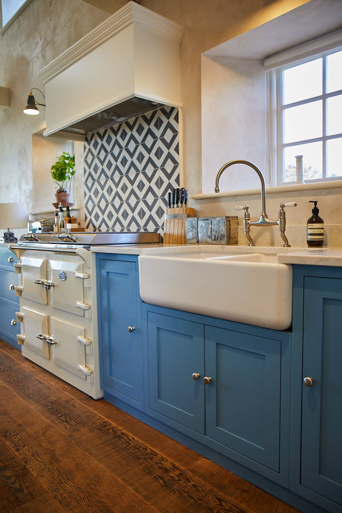 Bespoke light blue shaker kitchen cabinets with reclaimed pine wood floor