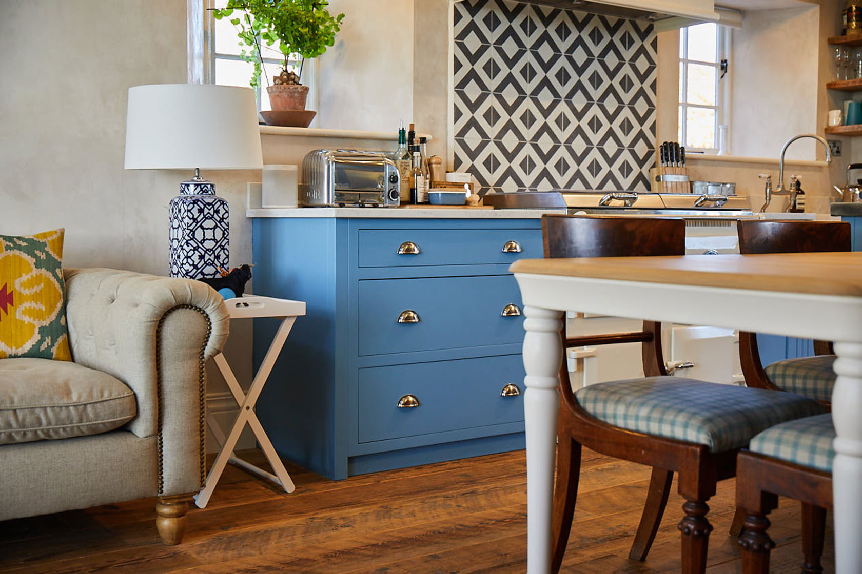 Light blue kitchen pan drawers with cream farmhouse table
