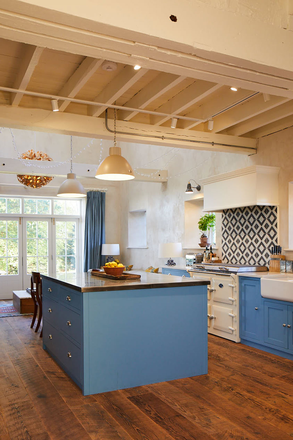Light blue kitchen island in open plan room with reclaimed pinewood floors