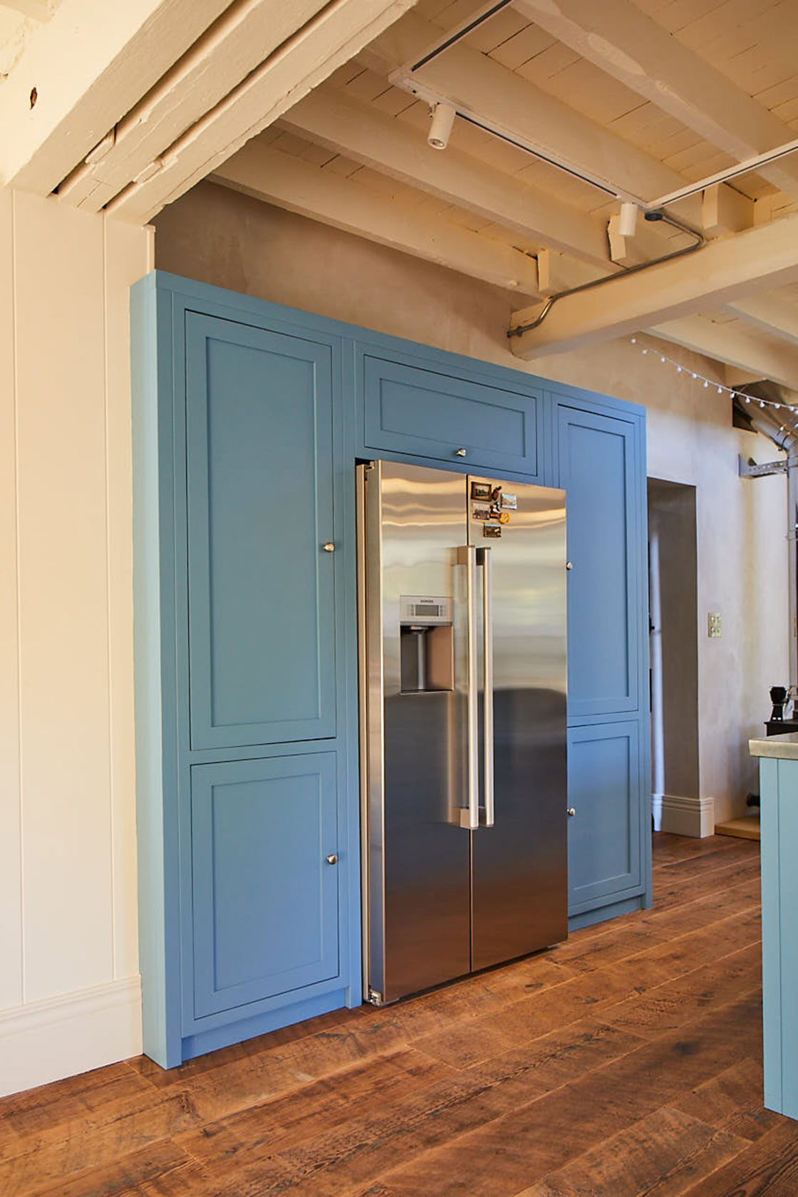 American stainless steel fridge freezer with tall painted light blue kitchen cabinets
