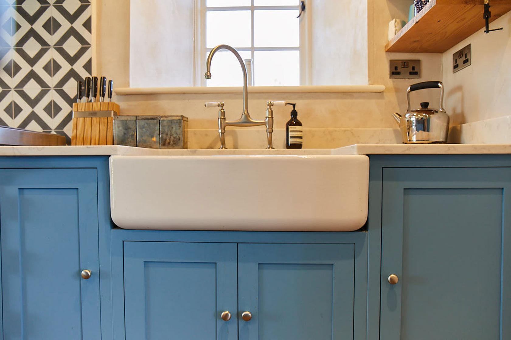 Double Belfast ceramic sink on light blue bespoke kitchen units