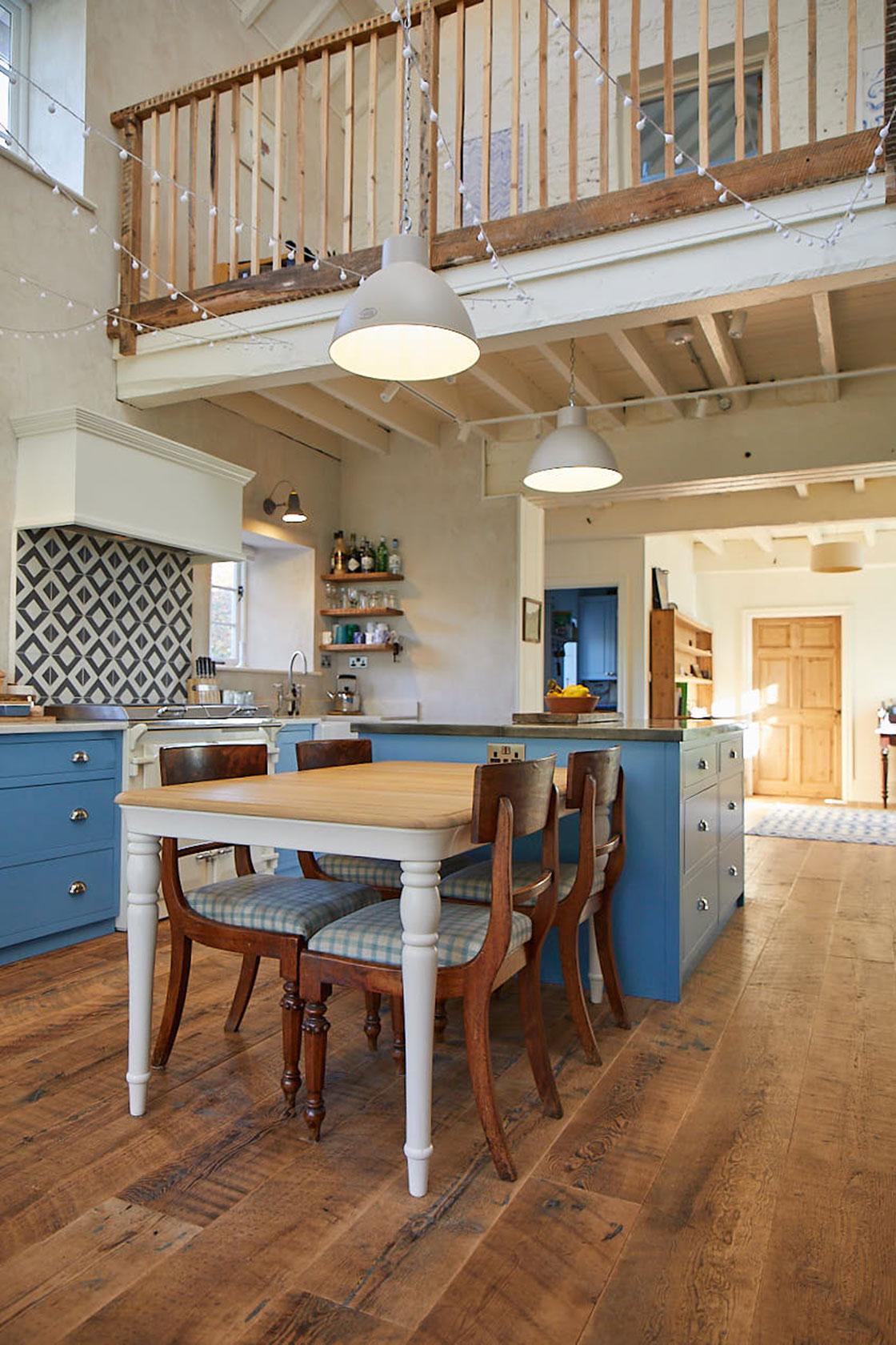 Painted farmhouse oak table next to light blue kitchen island