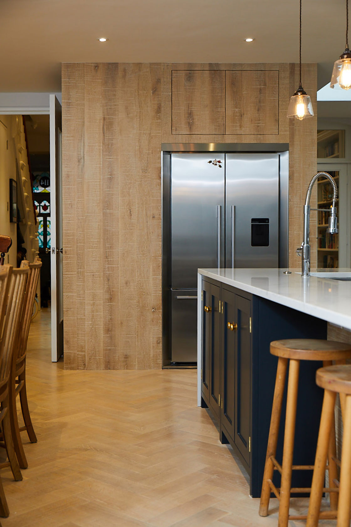 American Fisher & Paykel fridge freezer with surround in large limed oak kitchen units