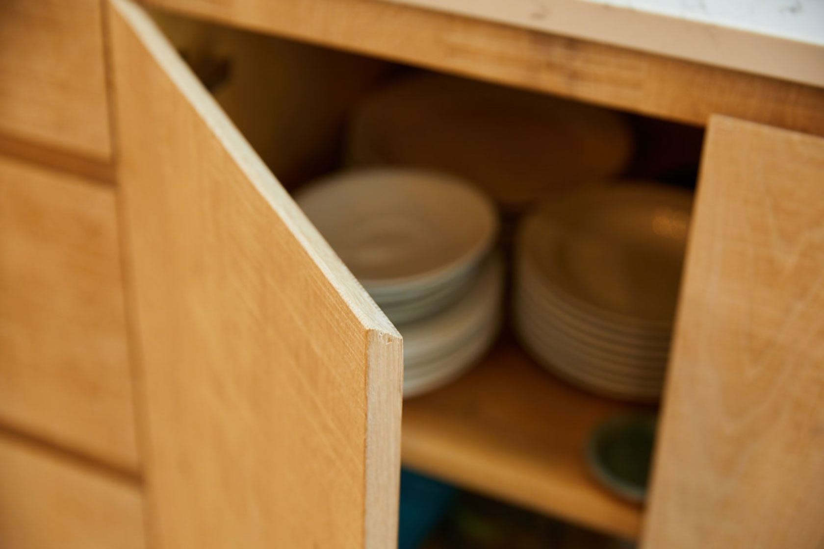 Close up chamfer handle built in to limed oak slab kitchen door