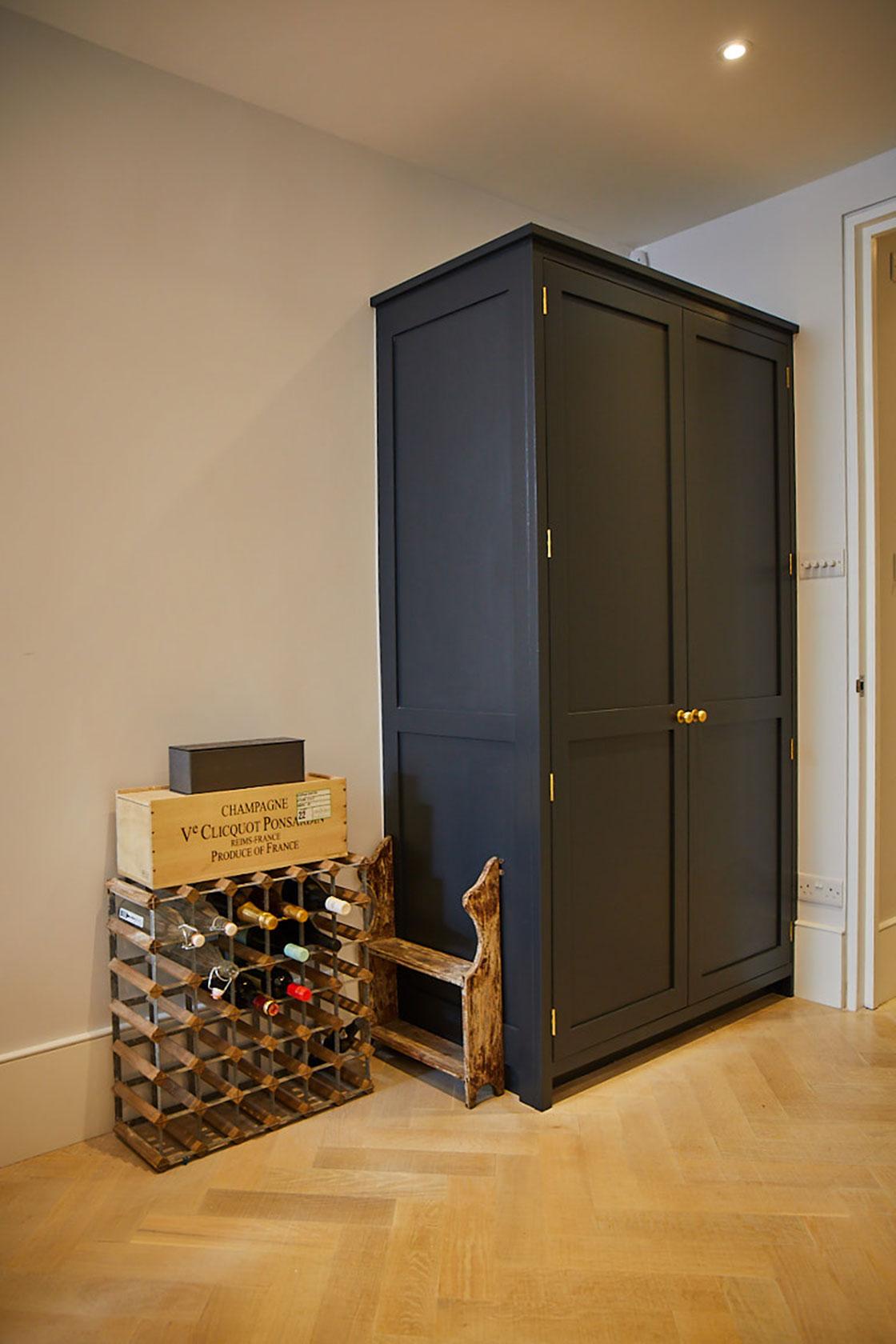 Tall dark blue larder cabinet next to open wine rack