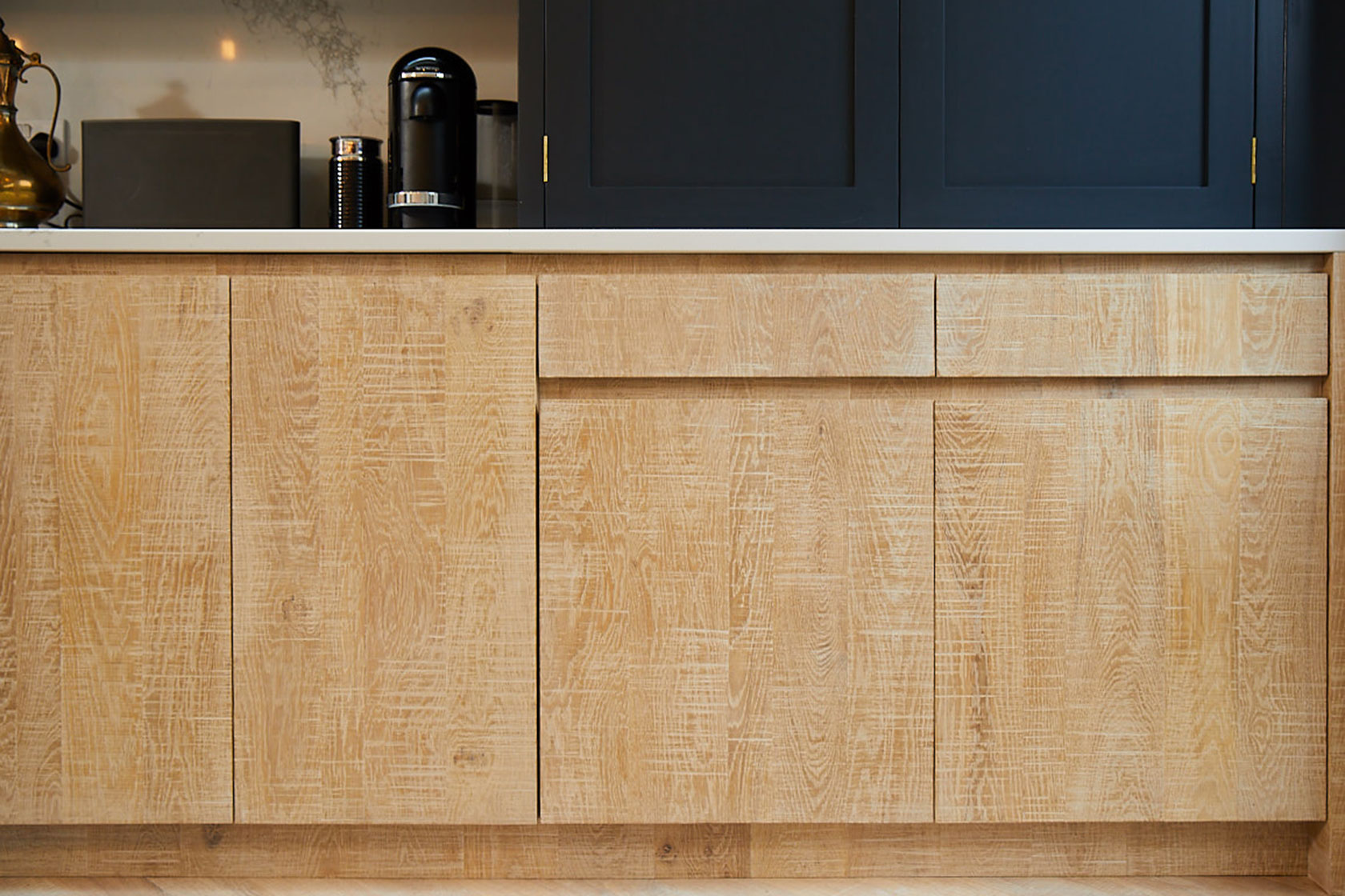 Limed oak kitchen base units with integrated bin for recycling and Caesarstone worktop